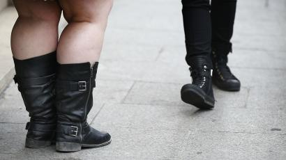 Two pairs of feet in boots.