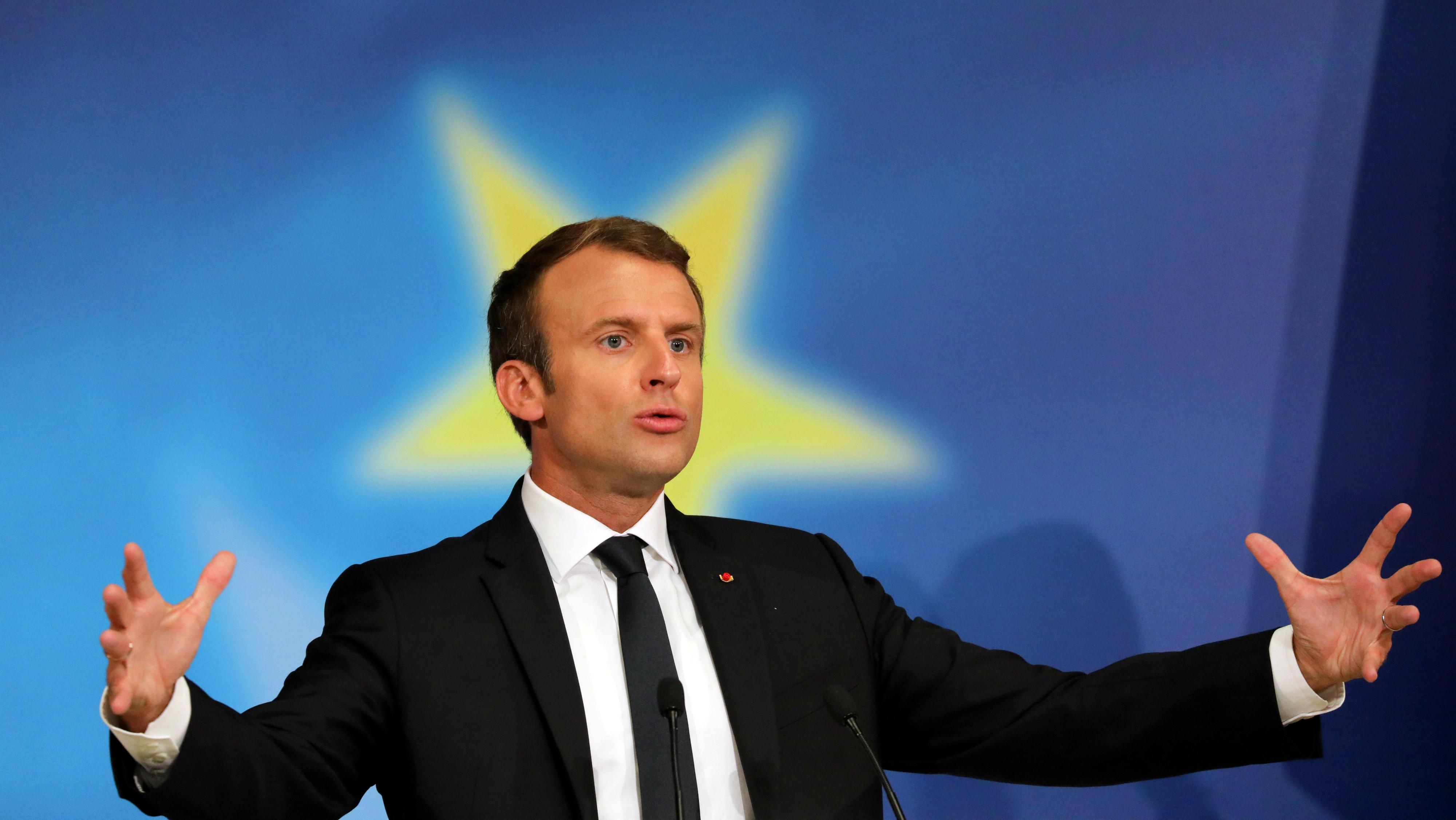 Emmanuel Macron at a lectern.