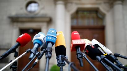 Microphones of various media outlets are seen outside the German Parliamentary Society offices