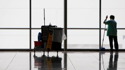 A cleaner mops the floor of an empty hall at a convention centre in Singapore