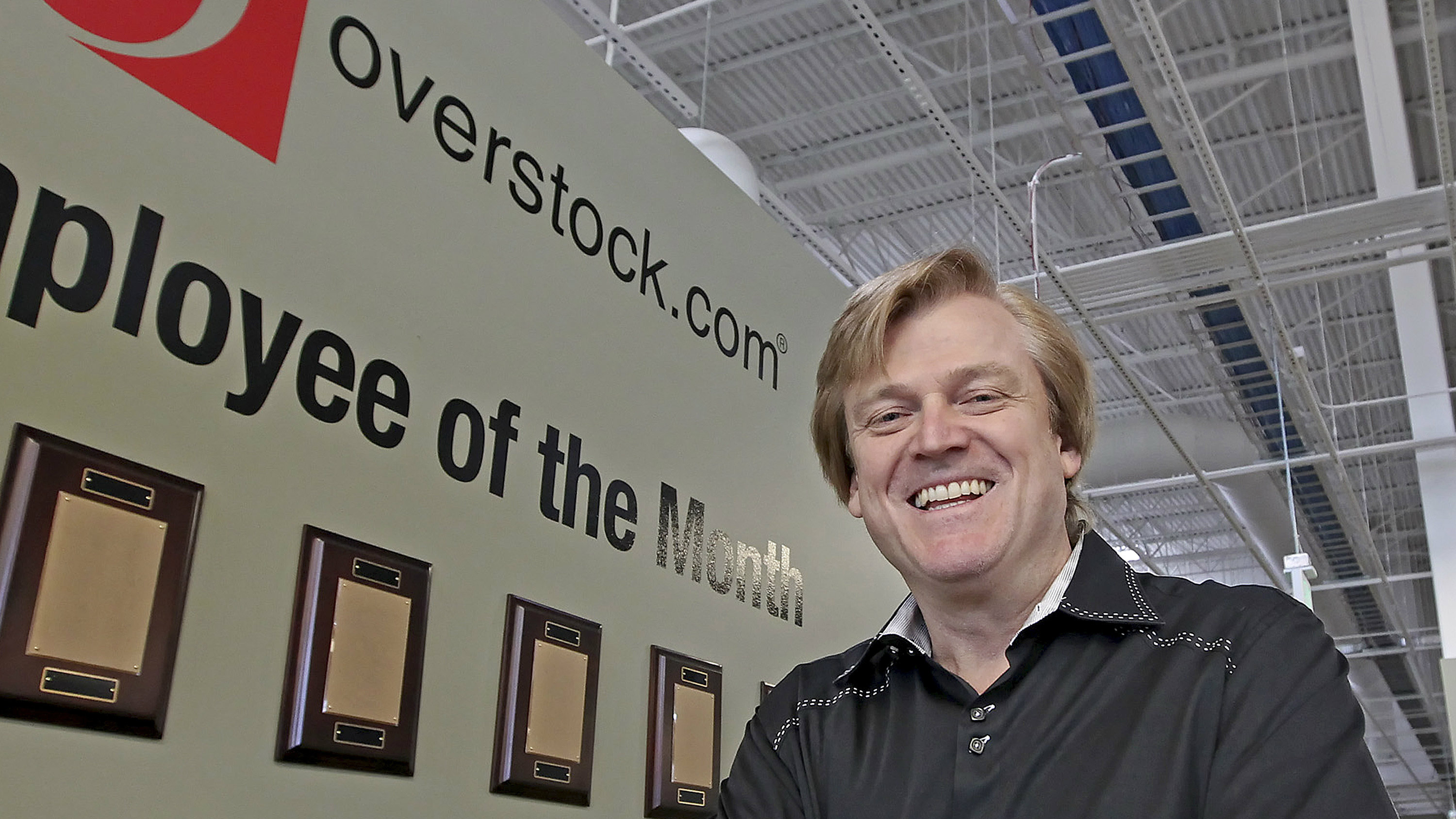 This March 25, 2010 file photo, Chairman and CEO of OverStock.com Patrick Byrne poses for a picture by the employee of the month wall at the warehouse of Overstock.com outside of Salt Lake City, Utah. Emboldened by the new White House administration, advocates including Byrne, the money man behind Utah's ambitious voucher proposal that was crushed by voters a decade ago, say there is a renewed appetite to expand school choice in the state.
