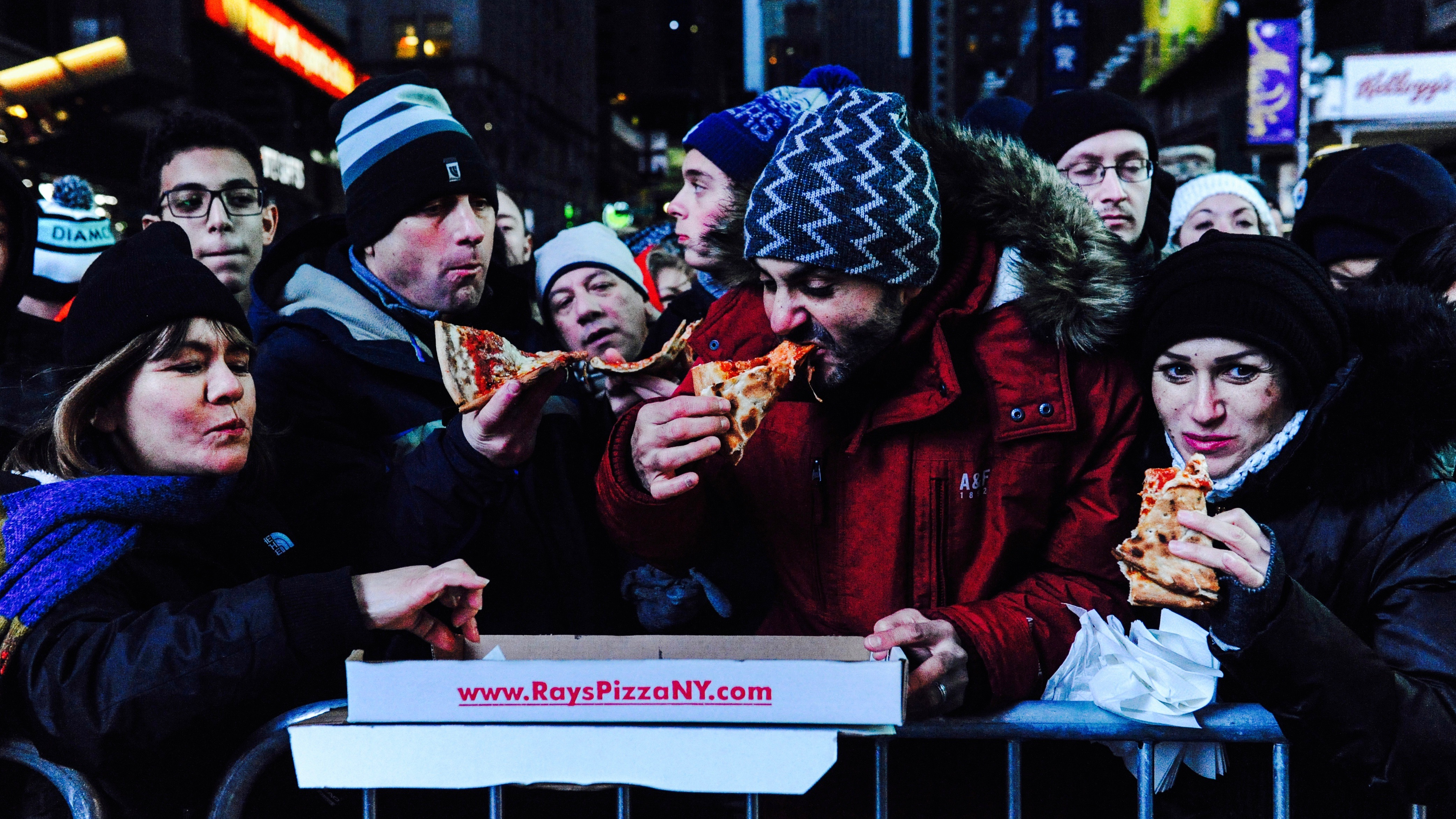 People eating pizza outside in NYC.