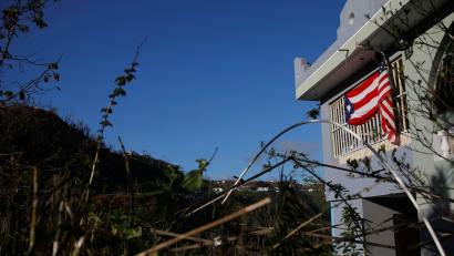 The U.S. and Puerto Rico flags hang from a home affected by Hurricane Maria