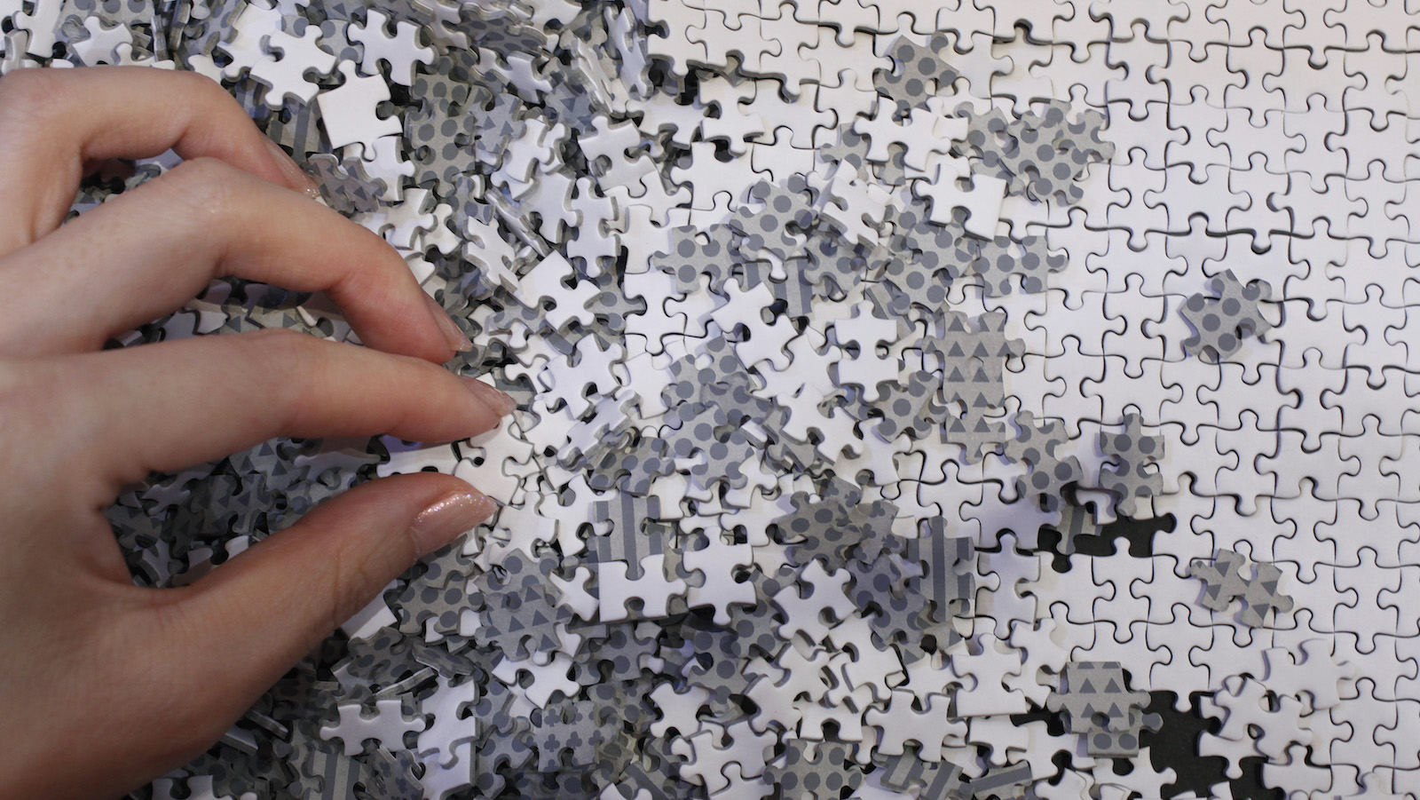 An employee of puzzle maker Beverly holds a piece of the company's white micro 1000 piece jigsaw puzzle at the International Toy Show in Tokyo June 14, 2012. The four-day event will open to public on Saturday, showcasing a total of about 35,000 products by 144 toy manufacturers. REUTERS/Yuriko Nakao (JAPAN - Tags: SOCIETY) - GM2E86E1IIS01