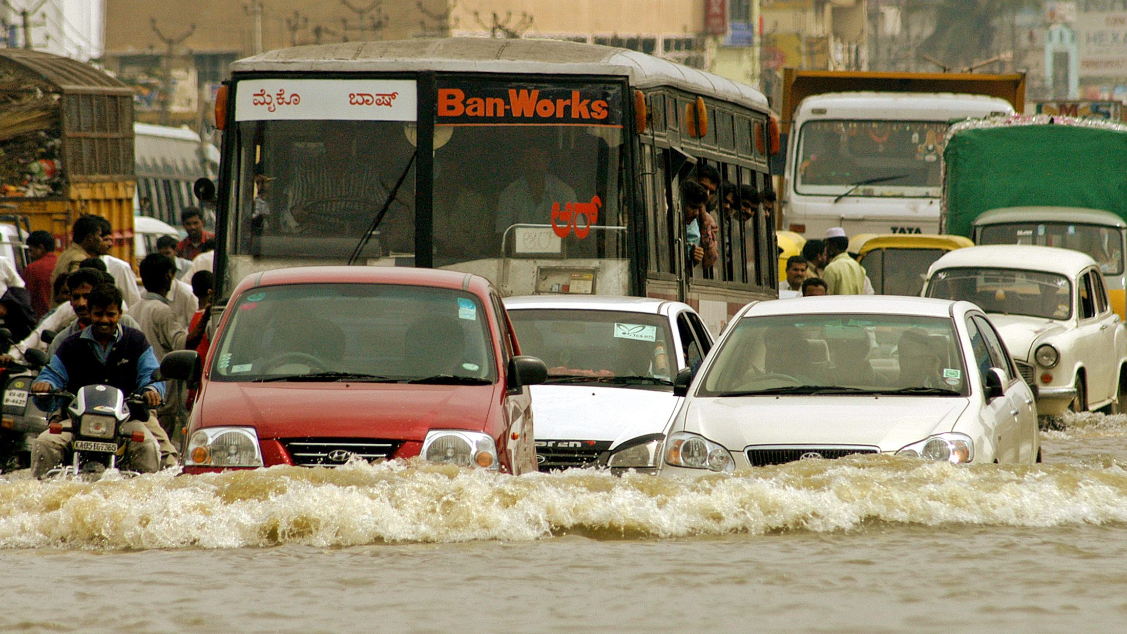 Vehicles move through a flooded road in the southern Indian city of Bangalore October 24, 2005. Heavy rain swamped parts of southern India and disrupted traffic.