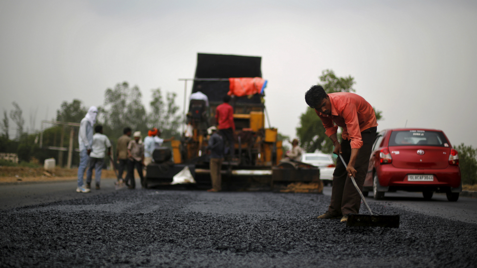 A labourer works at the construction site of the Delhi-Jaipur national highway in Manesar in the northern state of Haryana, India, July 9, 2015. To match insight INDIA-INFRASCTRUCTURE/