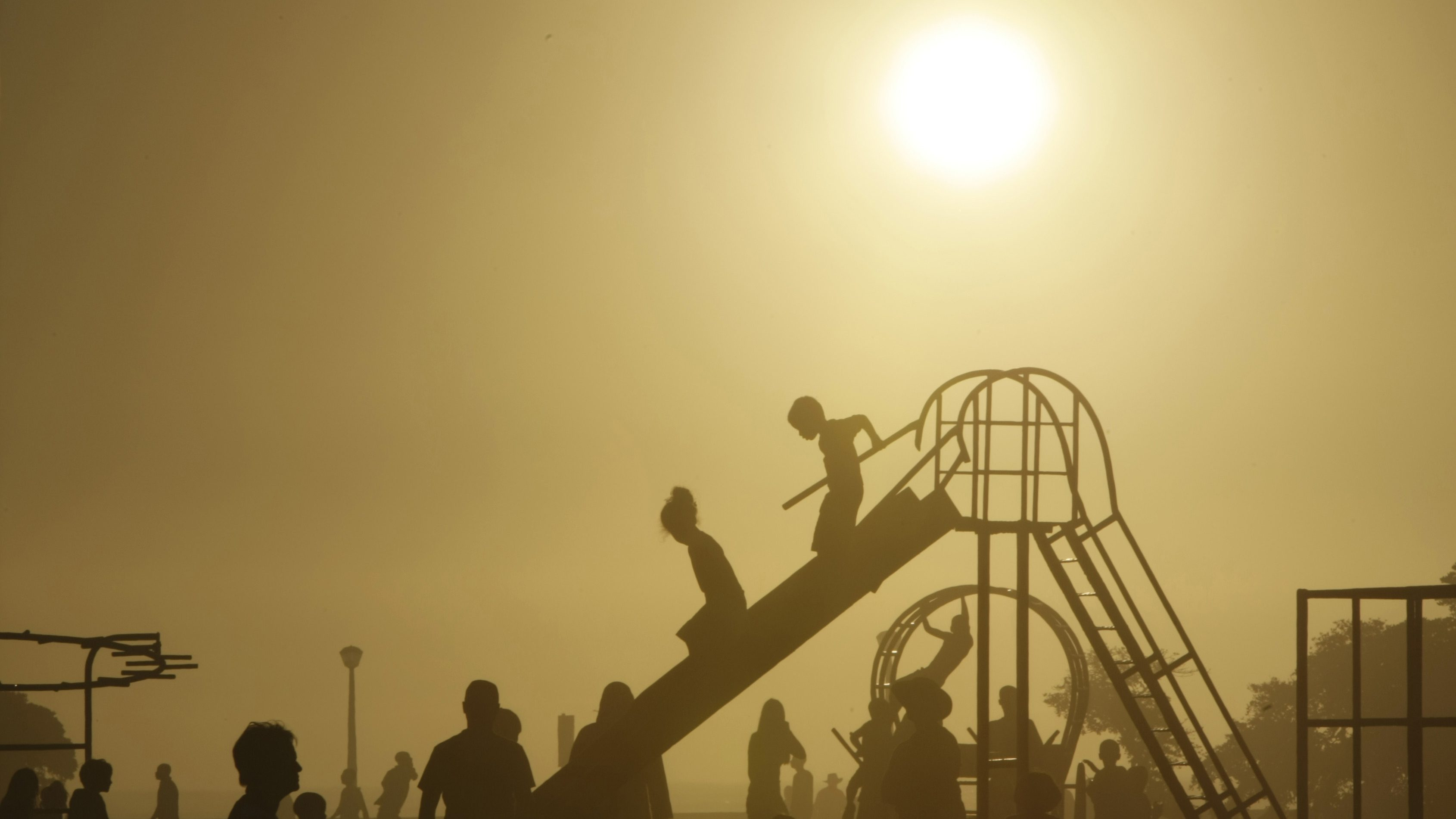 Children play as seasonal mist shrouds the sun on Cape Town's Sea Point promenade, March 2, 2008.  REUTERS/Mike Hutchings (SOUTH AFRICA) - GM1E4330GIJ01