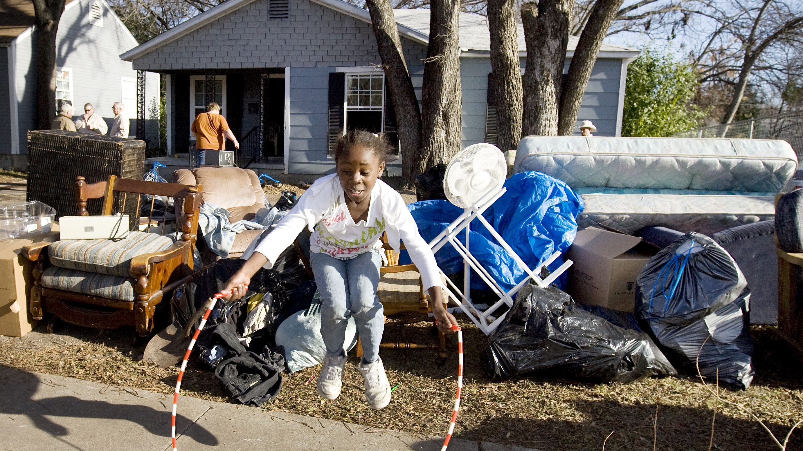 A young girl jumps rope on the sidewalk next to her family's belongings after she, her parents, and her four brothers and sisters, received a court order of eviction that was carried out by McLennan County Deputy Constables in Waco, Texas, December 31, 2008.        (UNITED STATES) - GM1E5110B5P01