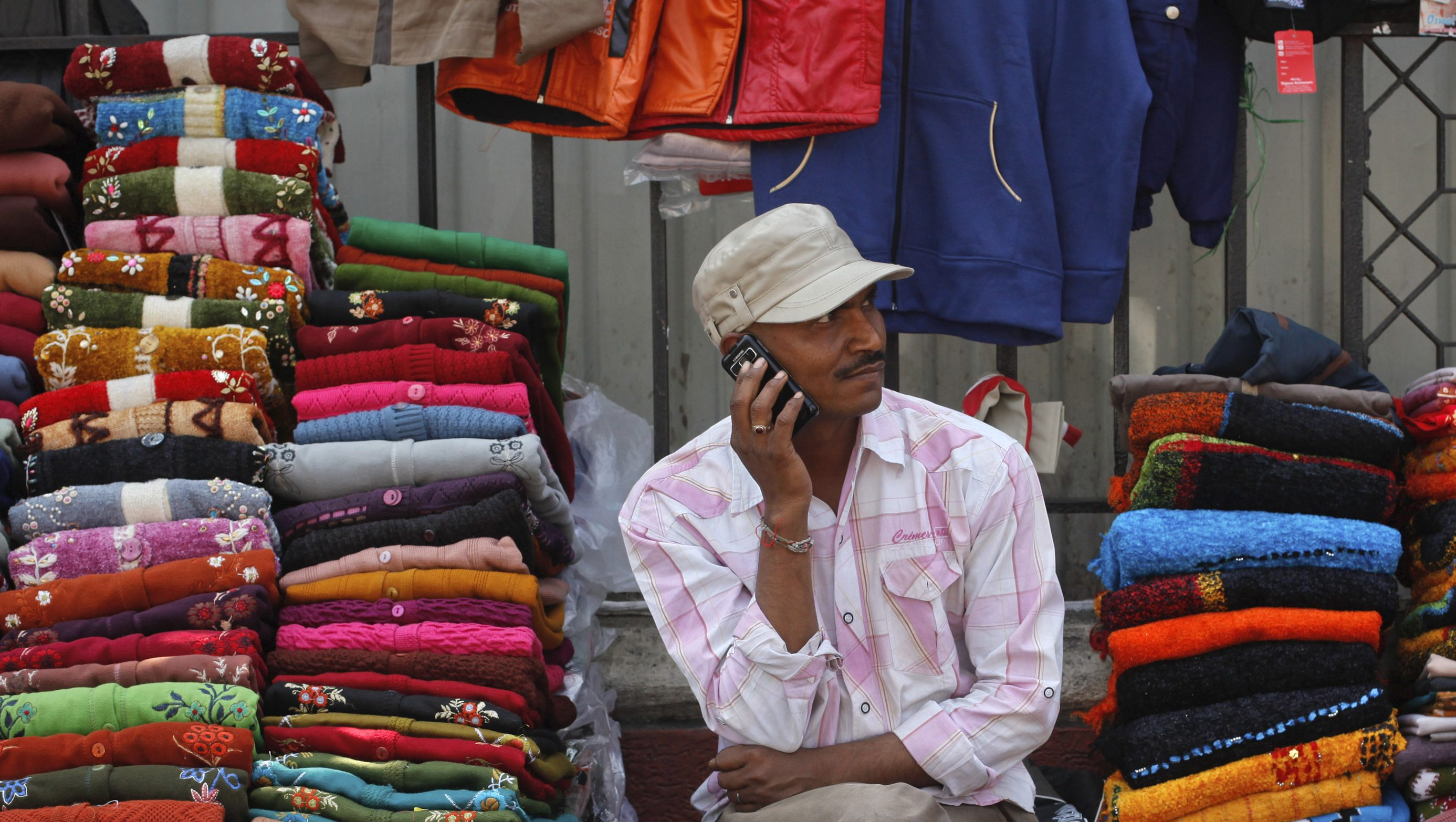 A vendor speaks on his mobile phone as he waits for customers at his roadside shop selling clothes in Mumbai