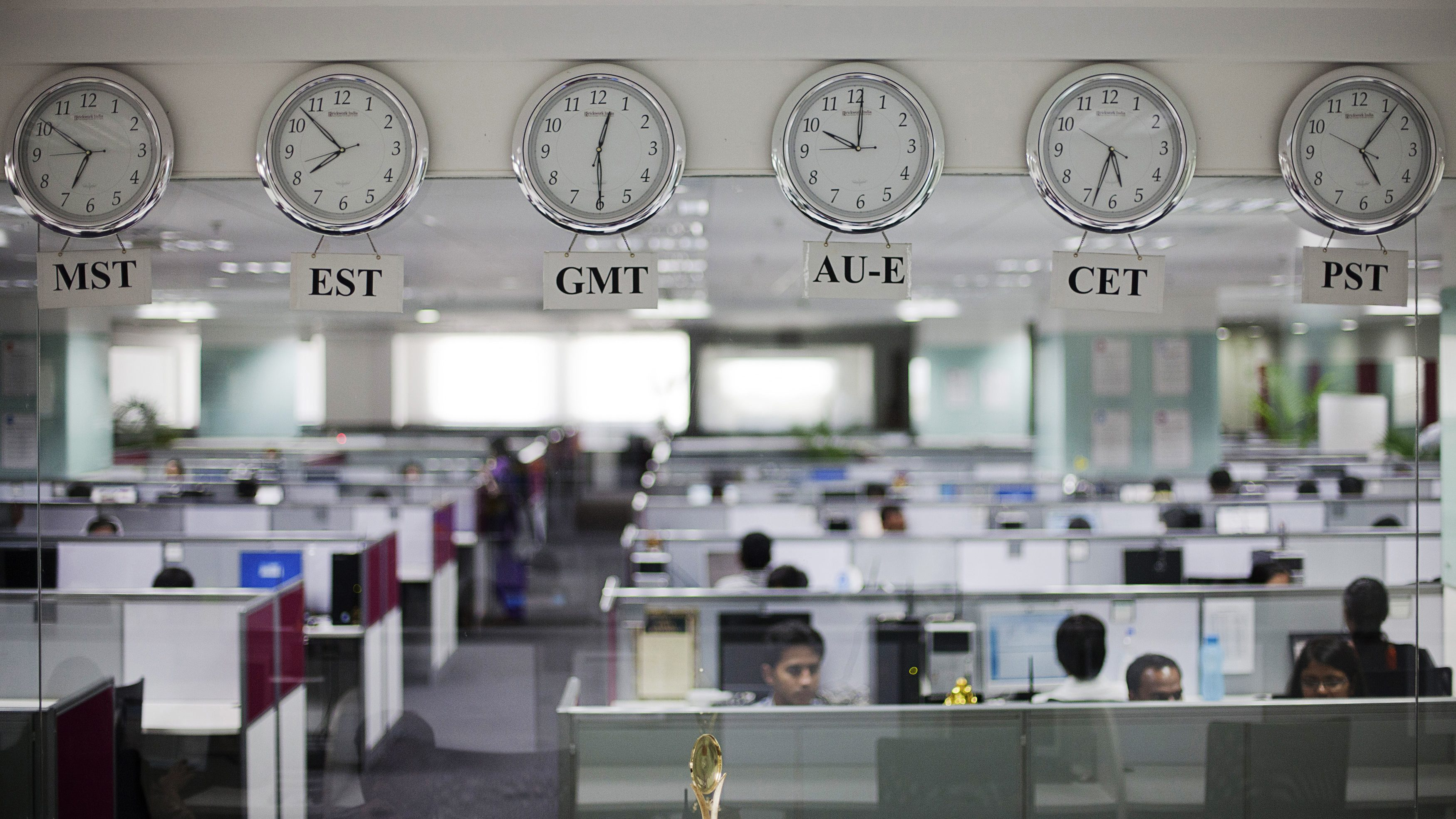 Workers are pictured beneath clocks displaying time zones in various parts of the world at an outsourcing centre in Bangalore February 29, 2012. The business of storing, decoding and analysing unstructured data - think video, Facebook updates, Tweets, Internet searches and public cameras - along with mountains of facts and figures can help companies increase profits, cut costs and improve service, and is now one of the world's hottest industries. It's called Big Data, and although much of the work is done in the United States, India is getting an increasing slice of the action, re-energising an IT sector whose growth has begun to falter. Picture taken February 29, 2012. REUTERS/Vivek Prakash (INDIA - Tags: BUSINESS EMPLOYMENT POLITICS) - GM1E8A80E5W01