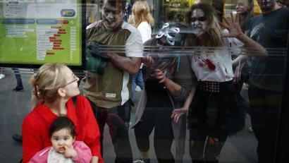 A woman and a child wait for a bus as actors dressed as zombies gesture for attention during a zombie walk in Belgrade.