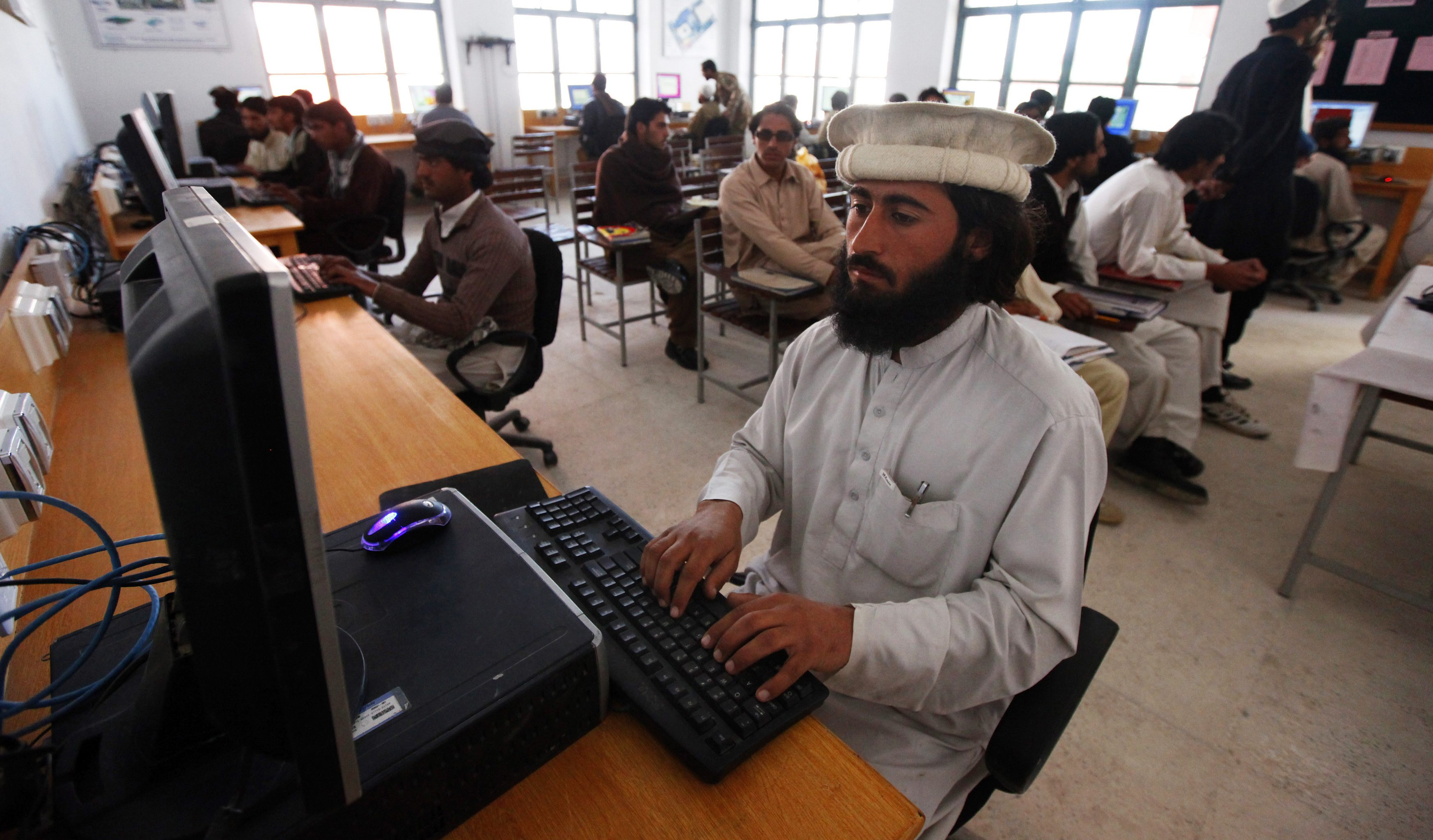 """A man attends a computer class at the Wana Institute of Technical Training in Wana, the main town in Pakistan's South Waziristan tribal region bordering Afghanistan November 27, 2012. In a Pakistan army base high in the mountains on the Afghan frontier, a general explains a strategy for fighting the Taliban he calls simply """"WHAM"""" - winning hearts and minds. According to the army narrative, the campaign includes winning over the region's ethnic Pashtun tribes through dialogue, creating commercial opportunities and providing education in new schools and colleges. To match Feature PAKISTAN-MILITARY/  Picture taken on November 27, 2012. REUTERS/Faisal Mahmood  (PAKISTAN - Tags: POLITICS CIVIL UNREST EDUCATION SCIENCE TECHNOLOGY MILITARY) - GM1E9231CL001"""
