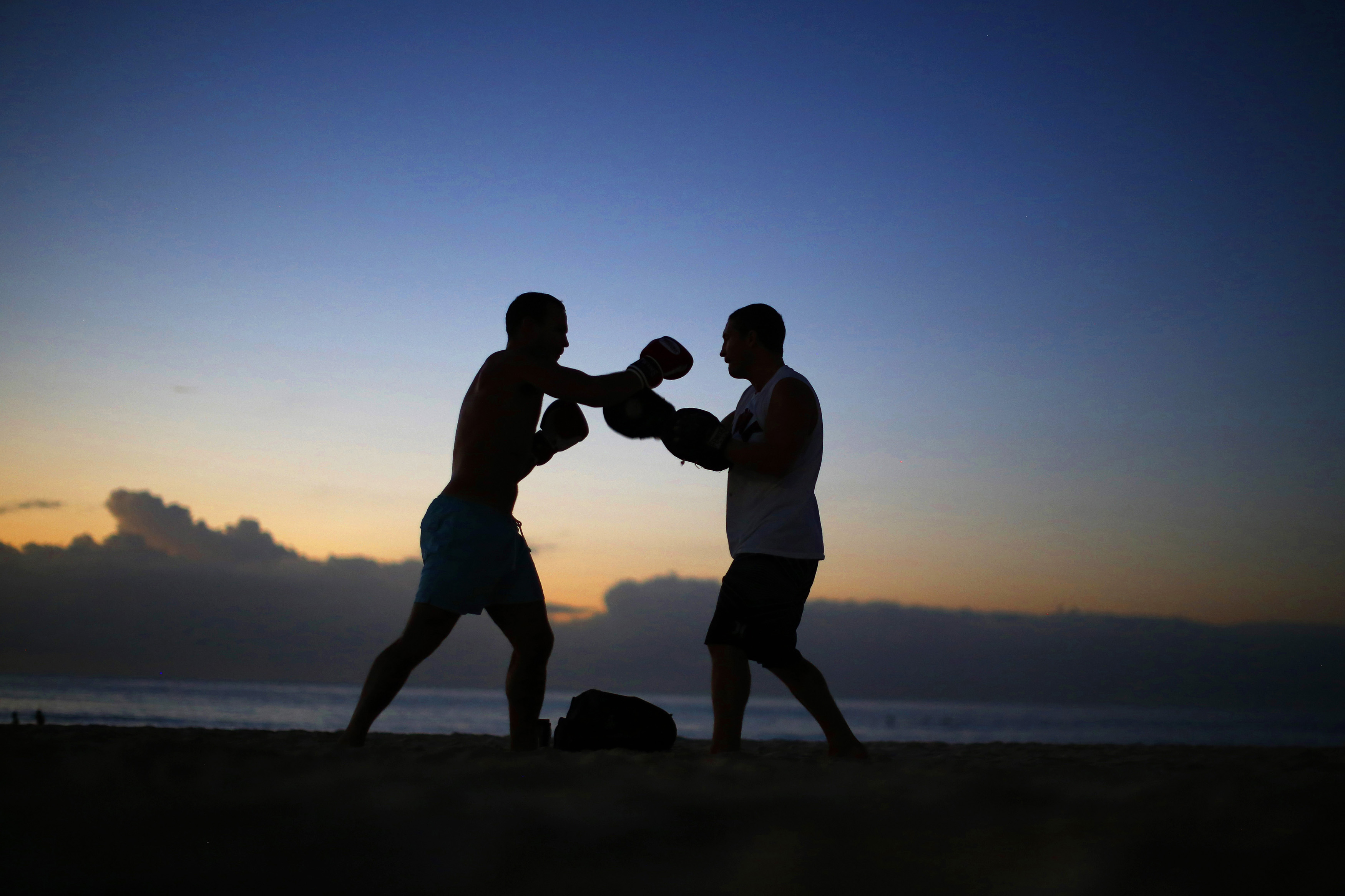 A boxer and his trainer practice before sunrise on Sydney's Bondi Beach