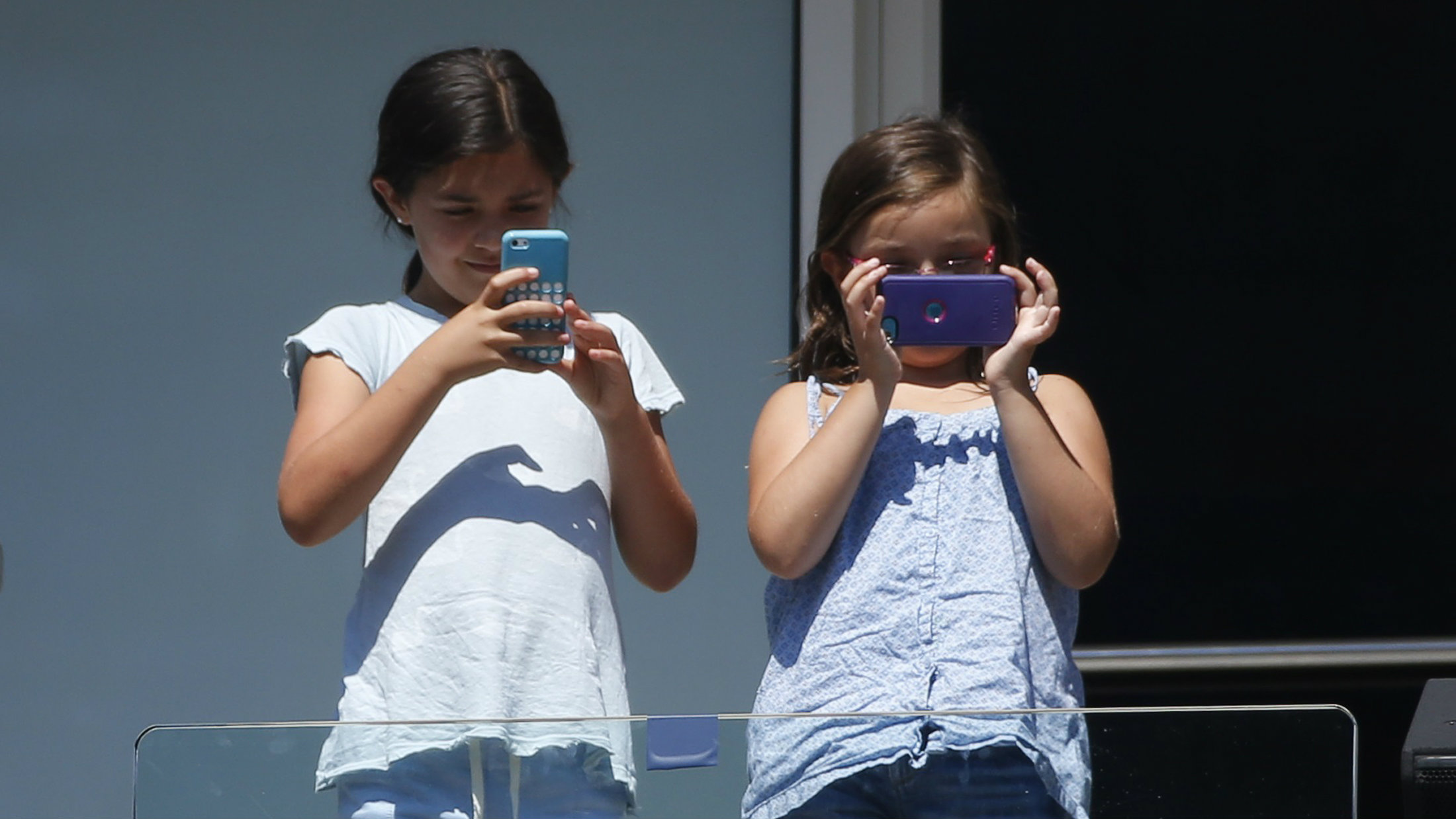 oung girls take pictures with the cell phones during the match between Victoria Azarenka of Belarus