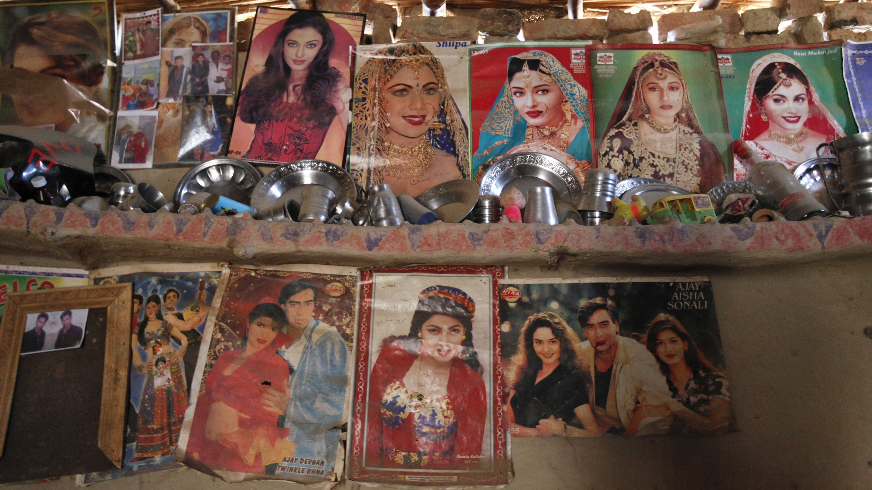 Utensils placed on a mud wall shelf adorned with Bollywood film star posters are seen in a room owned by a cotton picker's family in Meeran Pur village, north of Karachi November 23, 2014.  Women make up the bulk of Pakistan's half a million cotton producers, but labour rights activists say they are often exploited by overseers, who often withhold their wages and may subject some of them to sexual harassment. Many women work in Pakistan's cotton fields for less than $2 a day. Last year, a group of around 40 women decided their low wages could no longer cover food and clothing for their families so they did something almost unheard for poor working women in rural Pakistan - they went on strike.  REUTERS/Akhtar Soomro (PAKISTAN - Tags: AGRICULTURE BUSINESS COMMODITIES EMPLOYMENT SOCIETY POVERTY)   ATTENTION EDITORS: PICTURE 18 OF 27 FOR WIDER IMAGE PACKAGE 'UNITING PAKISTAN'S COTTON PICKERS'.   TO FIND ALL IMAGES SEARCH 'OVERSEERS SOOMRO' - LM2EAC315F201