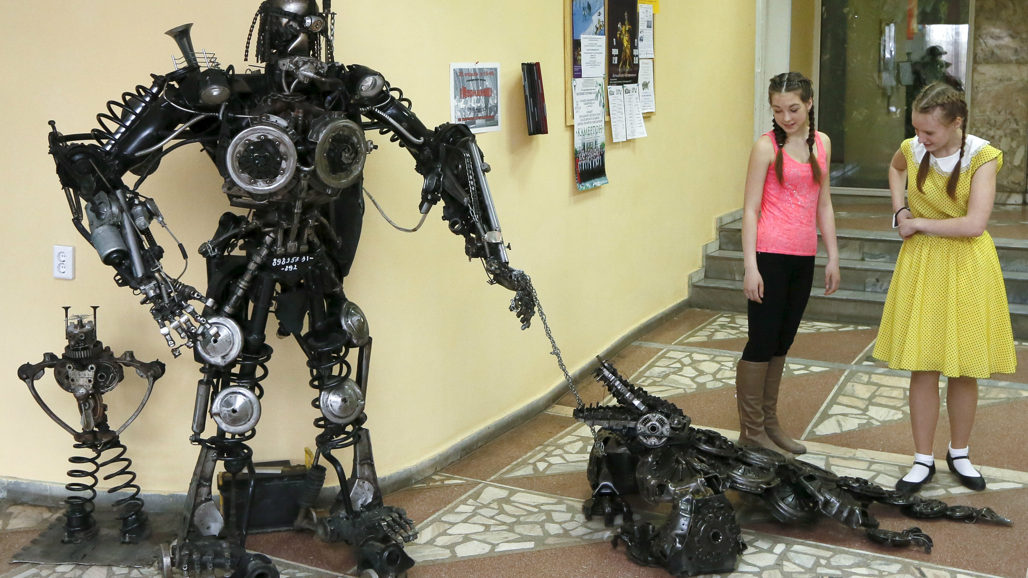 HEADLINE:Girls look at a robot and a crocodile made from used car components, created by mechanic and welder Sergei.