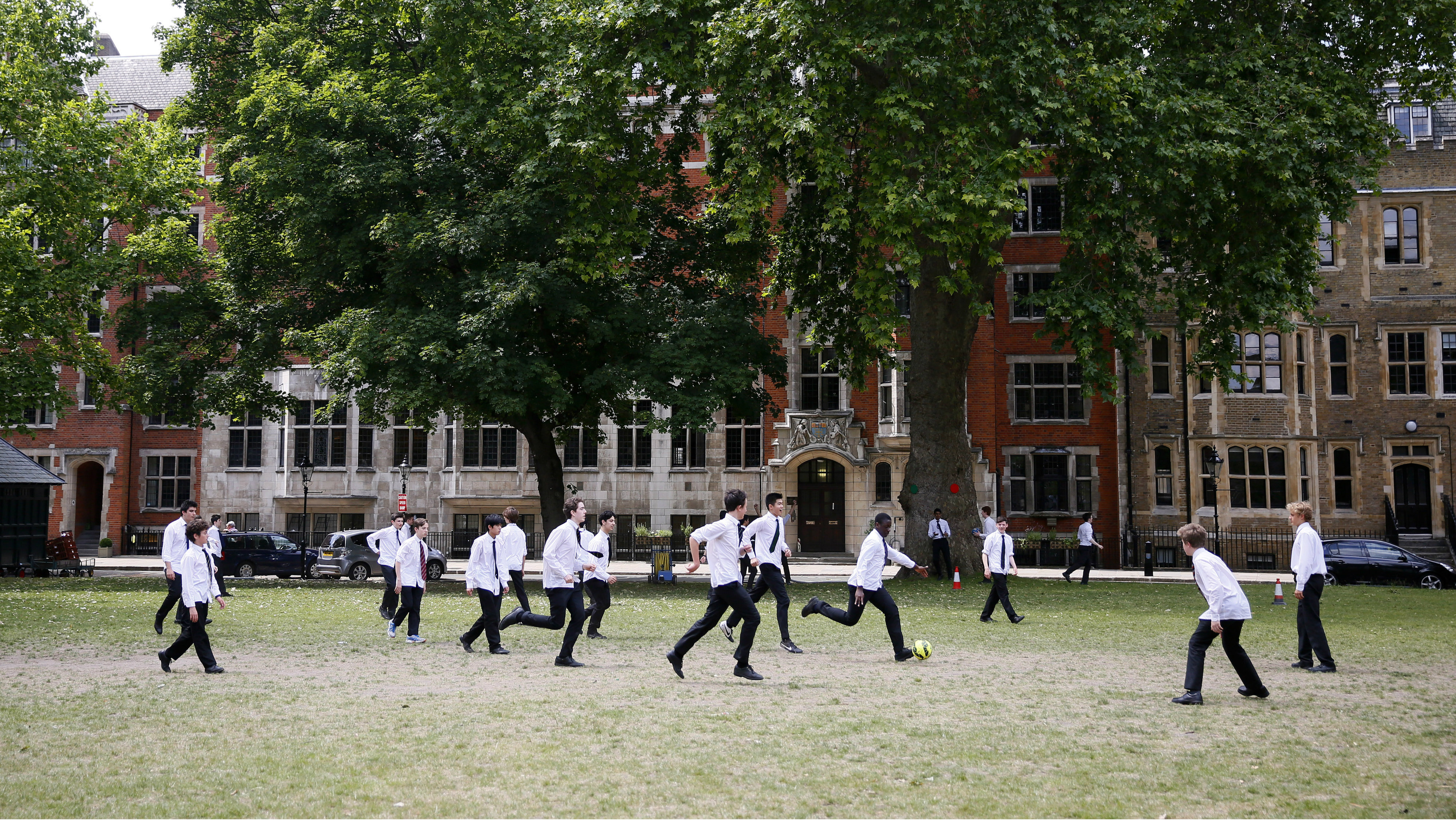 School children play soccer in Dean's Yard during lunch time on a summer day in central London