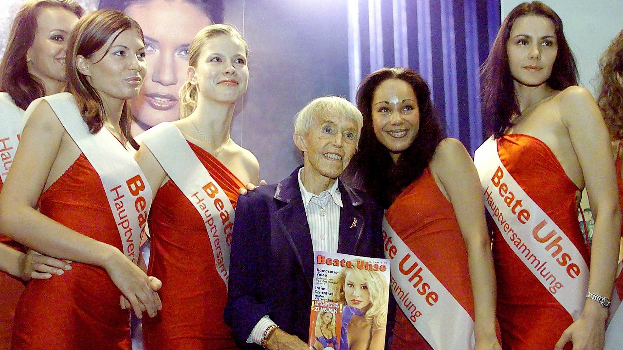 Beate Rotermund, 80-year-old head of international erotic company Beate Uhse AG, poses with models prior to the company's first shareholder meeting in the northern German city of Flensburg August 4, 2000. The company went public in 1999.