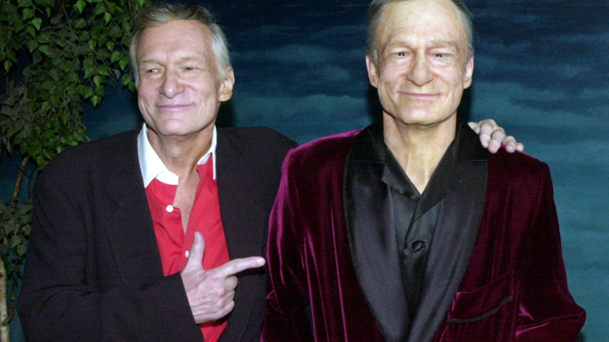 Hugh M. Hefner points as he poses next to a wax figure of himself February 20, 2001 during an unveiling ceremony at the Hollywood Wax Museum in Los Angeles. The wax figure will be enshrined in the museum to kick off a series of celebrations leading up to his 75th birthday in April.