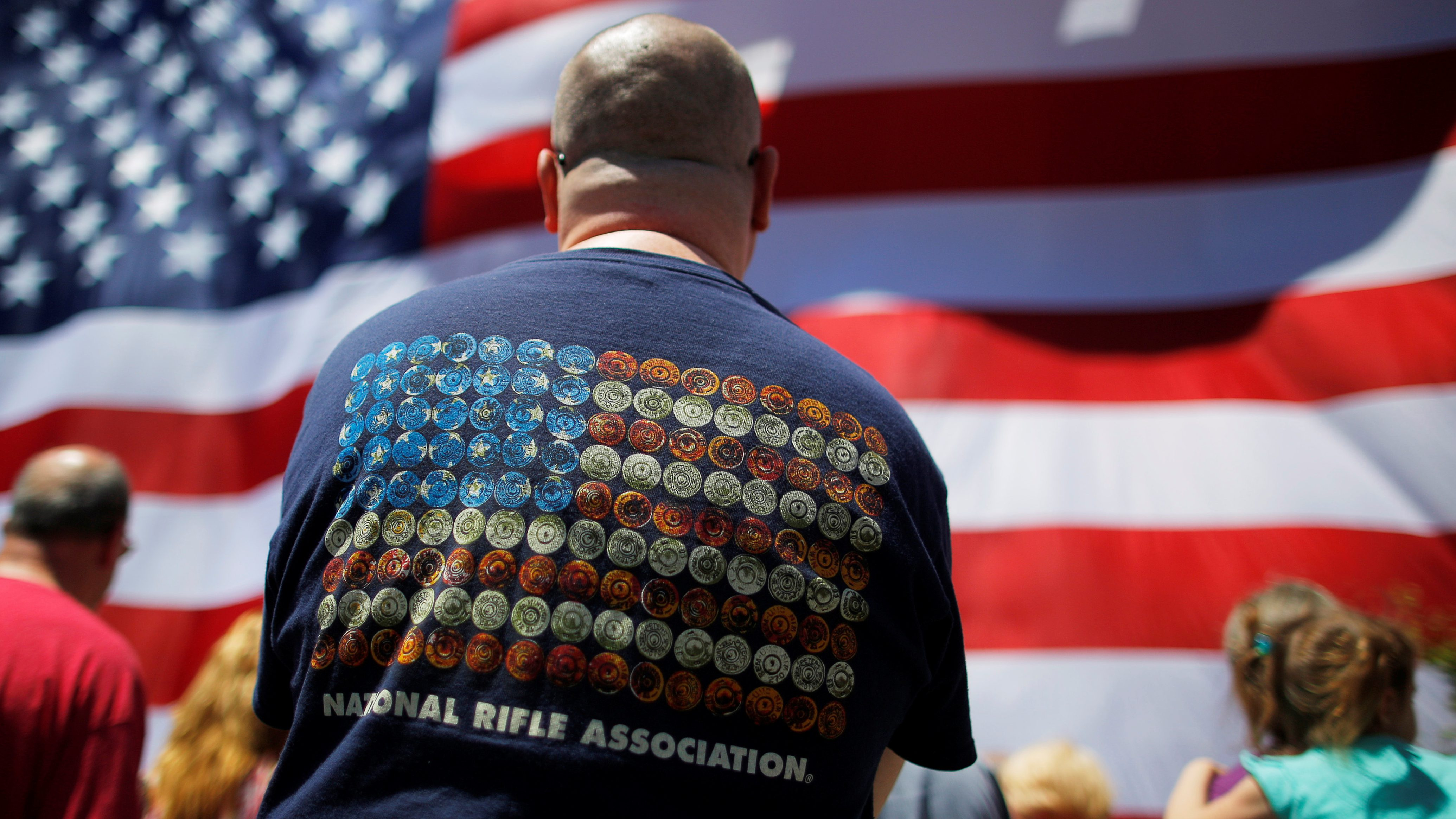 """Onlookers, including a man wearing a National Rifle Association (NRA) t-shirt, watch as a 95-by-50-foot American flag is unfurled on the side of an apartment complex, a replica of the """"The Great Flag"""" that was spun, woven, dyed, constructed and displayed on the same building by Amoskeag Manufacturing Company in 1914, in Manchester, New Hampshire, U.S., June 14, 2017.  REUTERS/Brian Snyder - RC1EDCBF4BB0"""