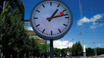 People walk past a giant replica of a station clock at a Swiss Rail company (SBB) administrative building in Bern
