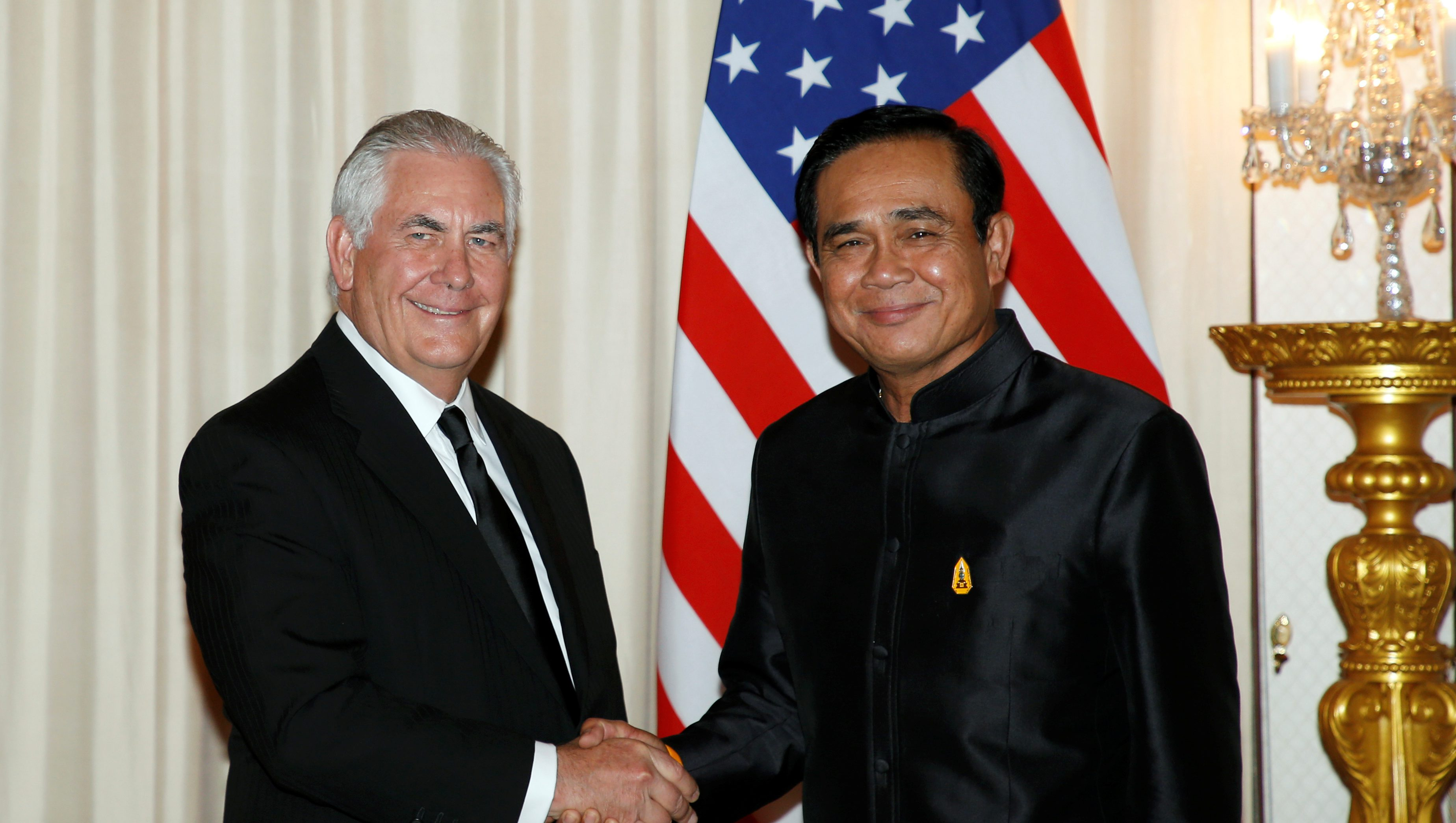 U.S. Secretary of State Rex Tillerson (L) shakes hands with Thai Prime Minister Prayut Chan-o-cha (R) during a meeting at Government House in Bangkok, Thailand August 8, 2017.  - RC1F42E94ED0