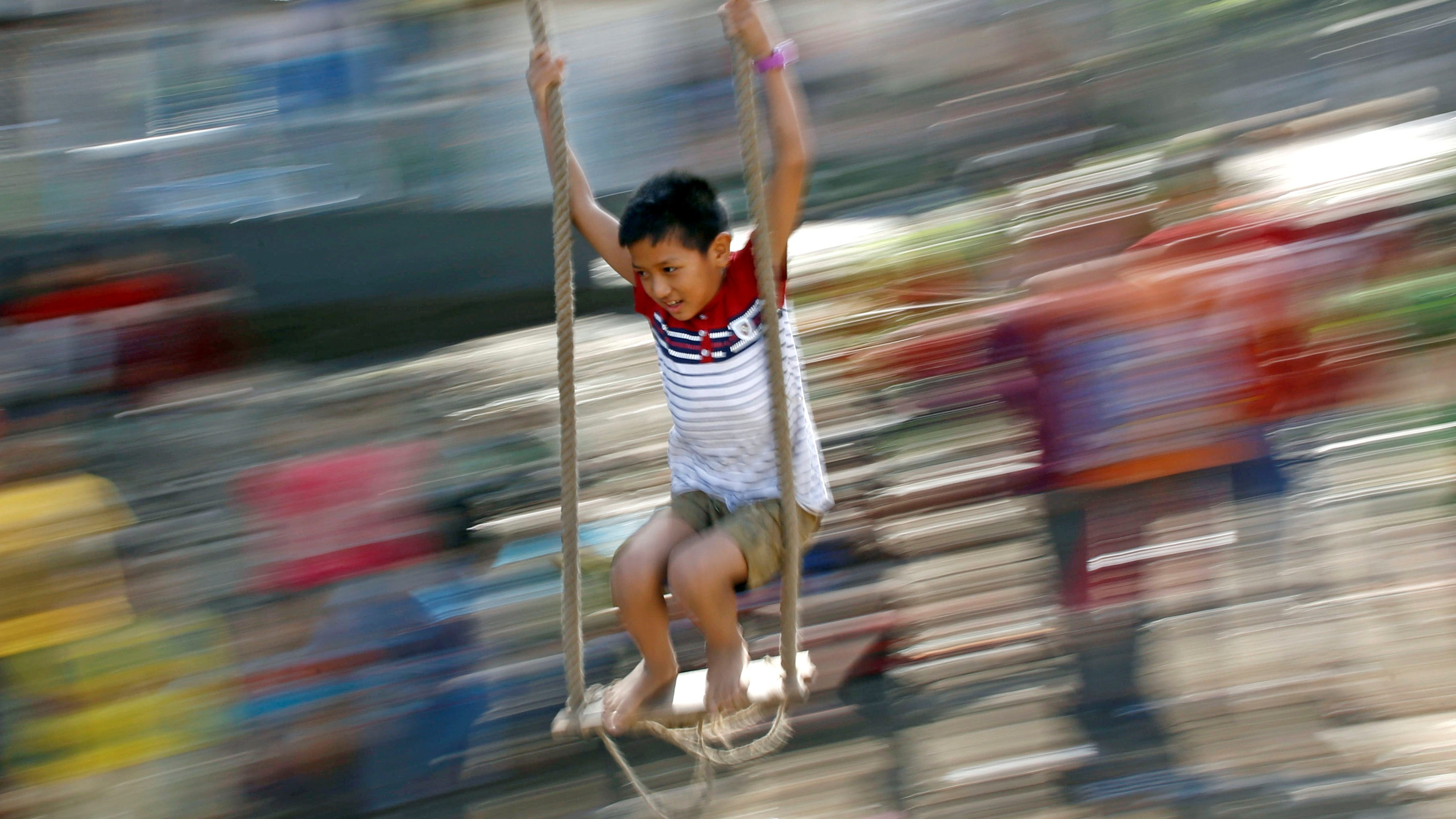A boy plays on a traditional swing during Dashain, the biggest religious festival for Hindus in Nepal, in Kathmandu, Nepal September 23, 2017.  - RC17E745CF90