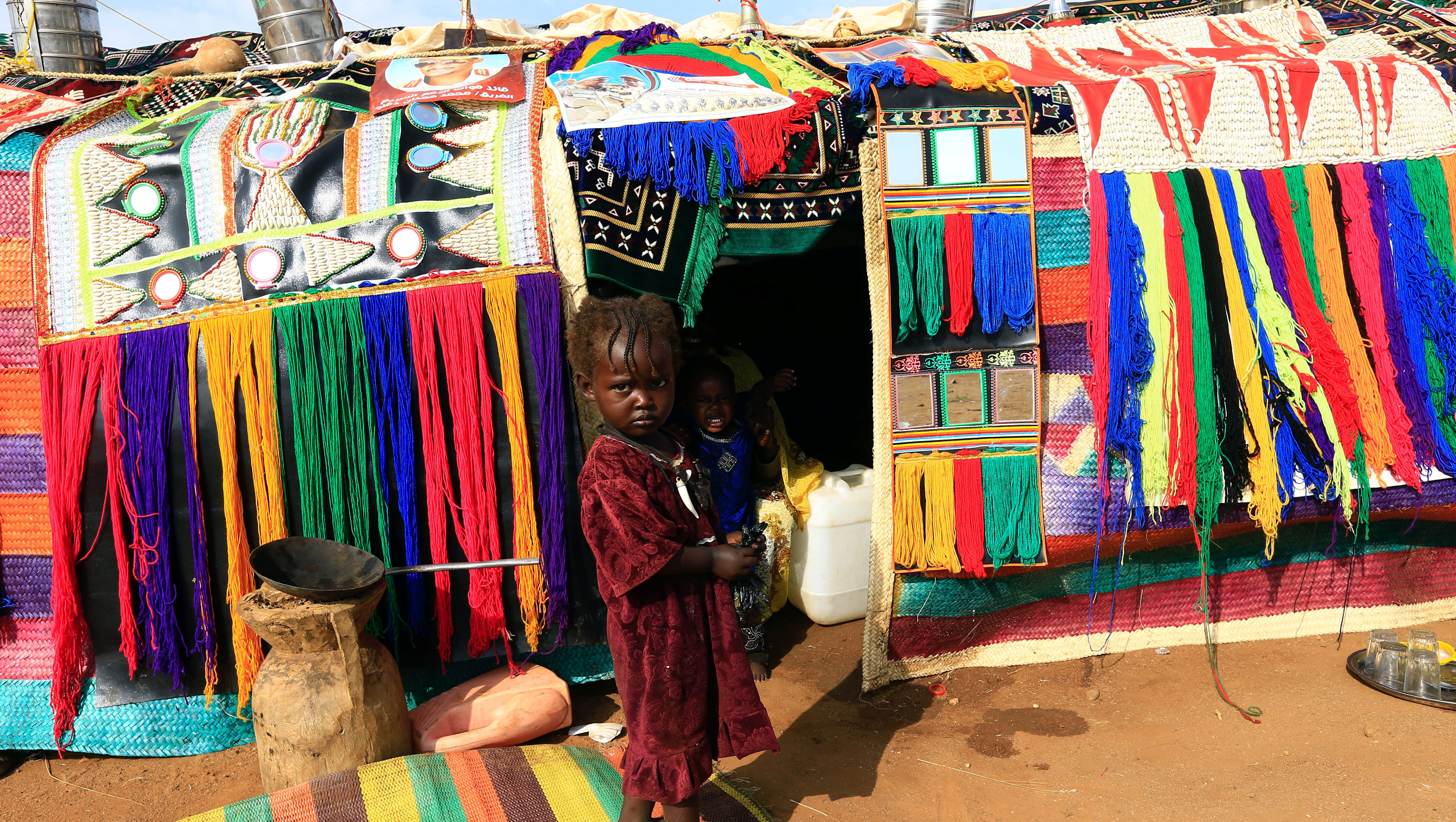 A child stands in front of a decorated house during Sudanese President's Omar al-Bashir visit to the war-torn Darfur region at Rapid Support Forces Headquarter in Umm Al-Qura, Darfur, Sudan September 23, 2017.