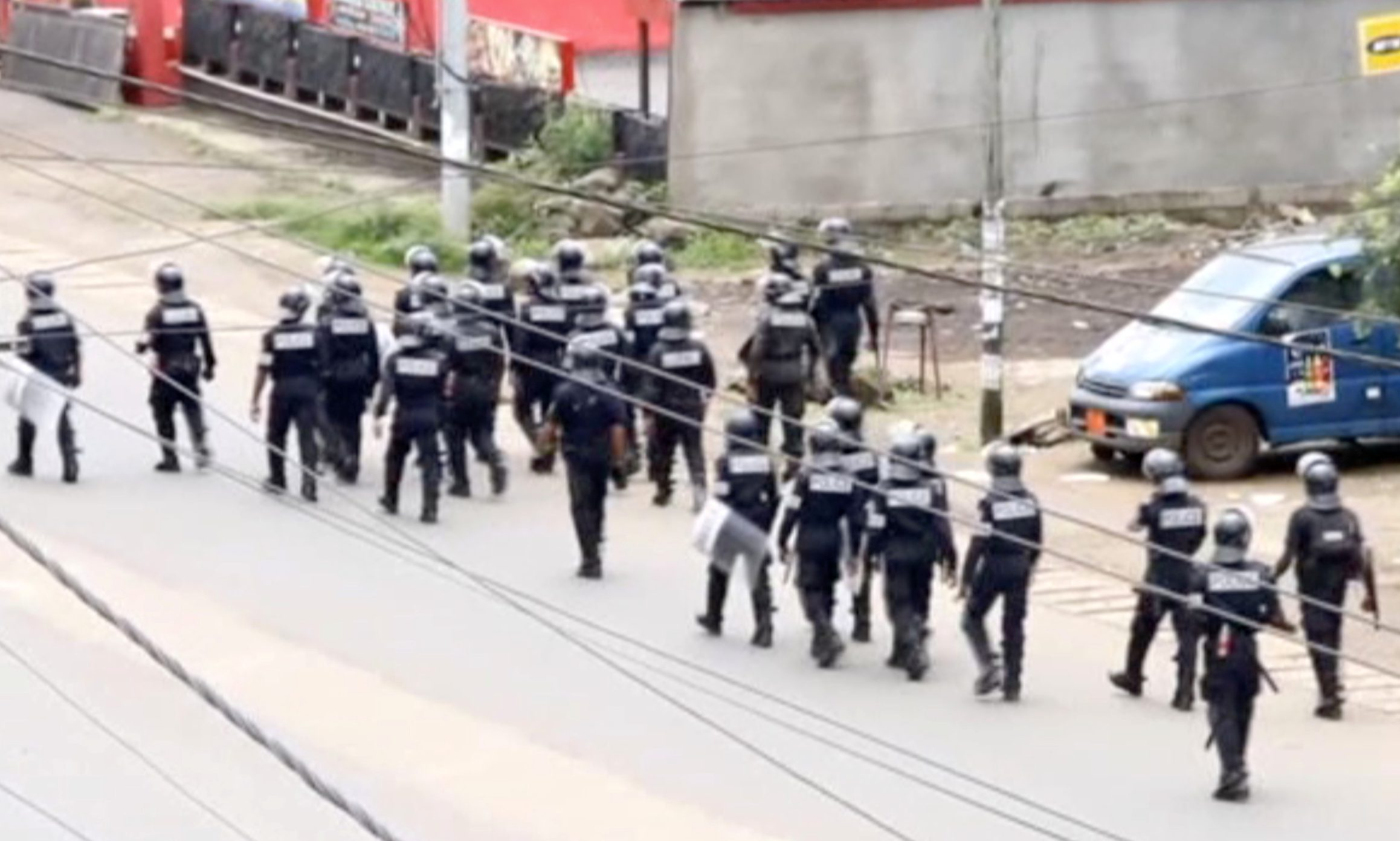 A still image taken from a video shows riot police walk along a street in the English-speaking city of Buea