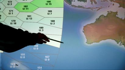 A member of staff at satellite communications company Inmarsat poses in front of a section of the screen showing the southern Indian Ocean to the west of Australia, at their headquarters in London March 25, 2014.