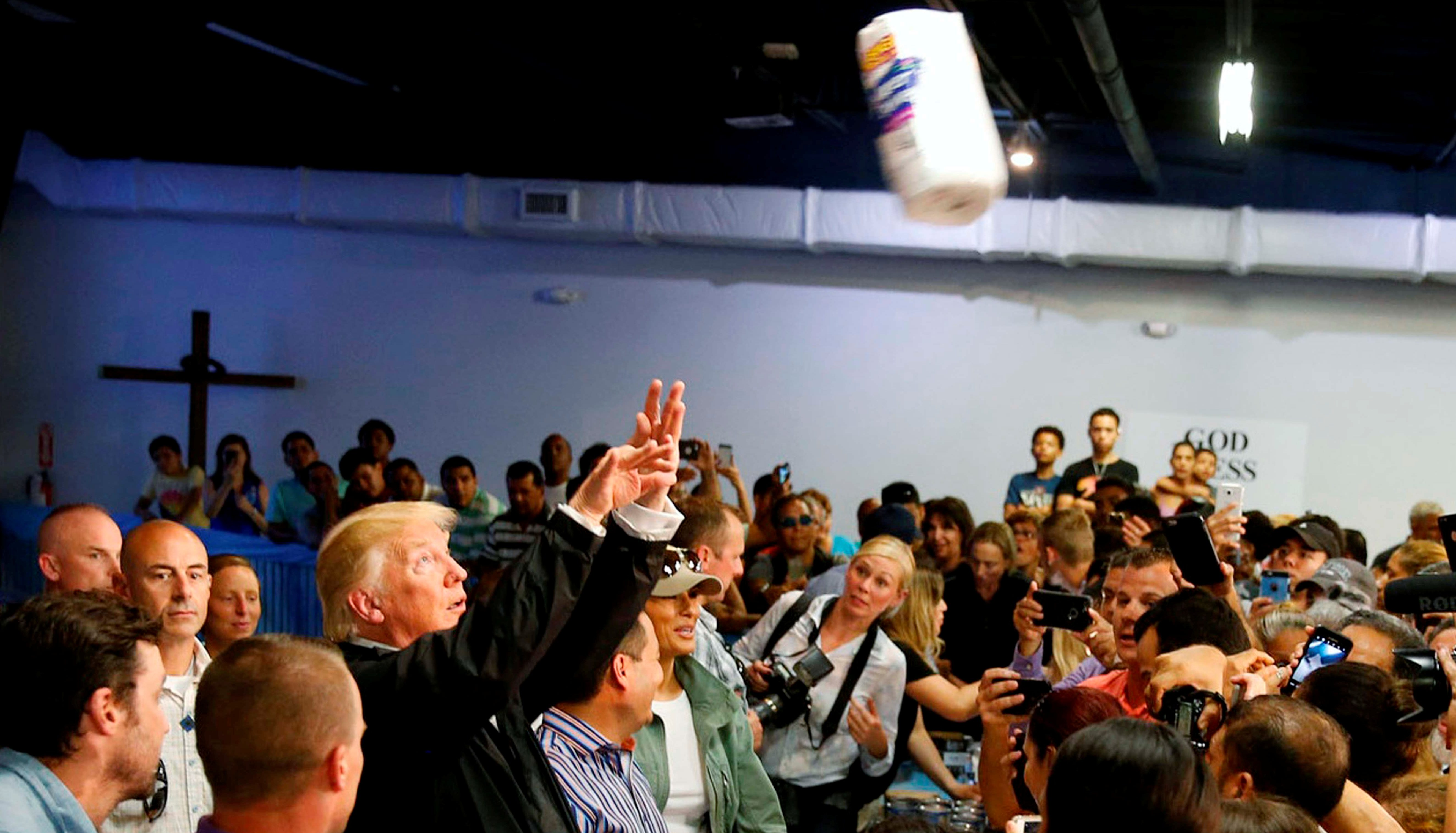 President Trump throws a roll of paper towels to residents gathered in a chapel while visiting areas damaged by Hurricane Maria in San Juan, Puerto Rico