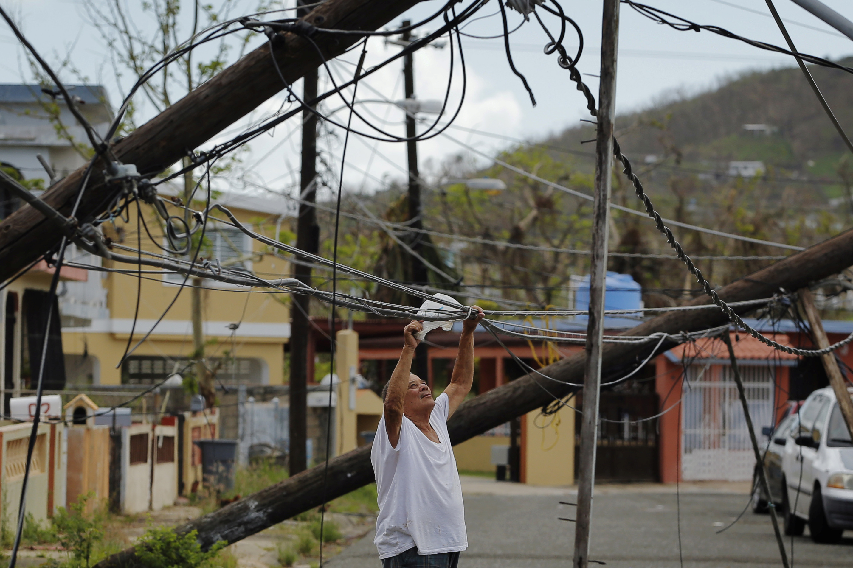A resident uses a plastic bag to move downed power cables so he can drive underneath them in a neighborhood following Hurricane Maria in Ceiba, Puerto Rico, October 4, 2017. Picture taken October 4, 2017.