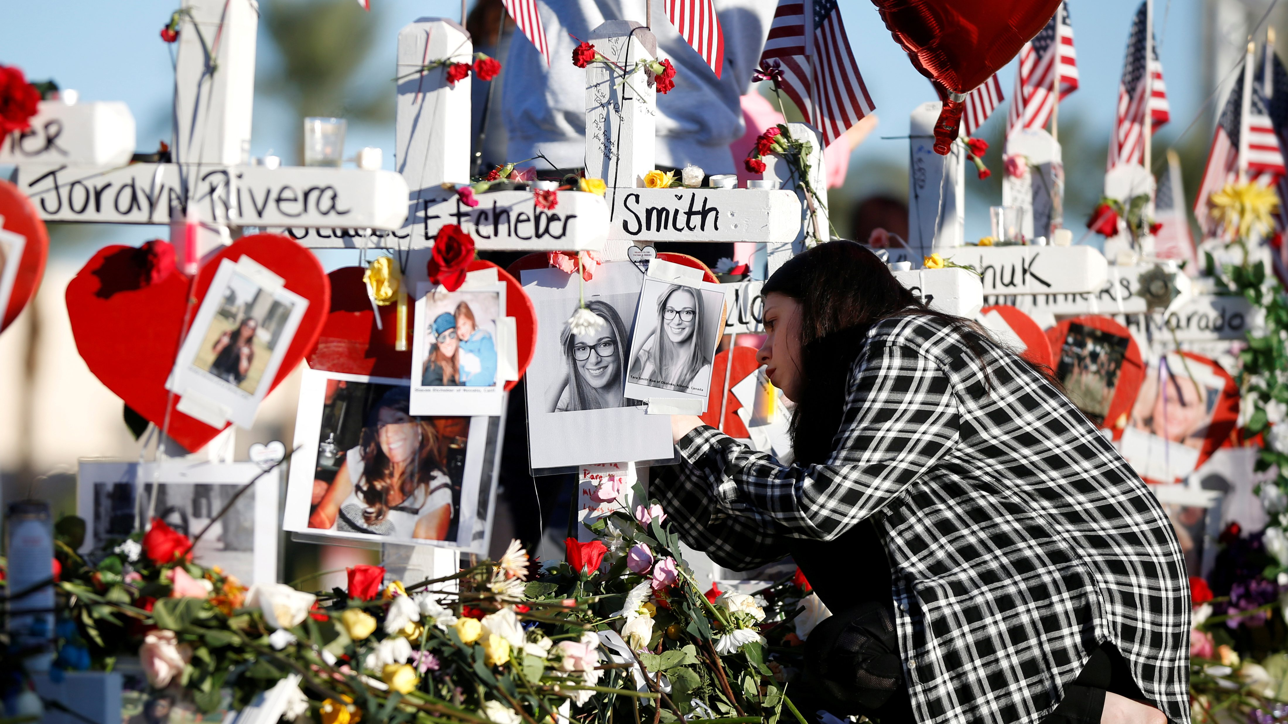 A woman writes a message on one of the white crosses set up for the victims of the Route 91 Harvest music festival mass shooting in Las Vegas, Nevada, U.S., October 7, 2017. REUTERS/Chris Wattie NO RESALES. NO ARCHIVE     TPX IMAGES OF THE DAY - RC146FB0A140