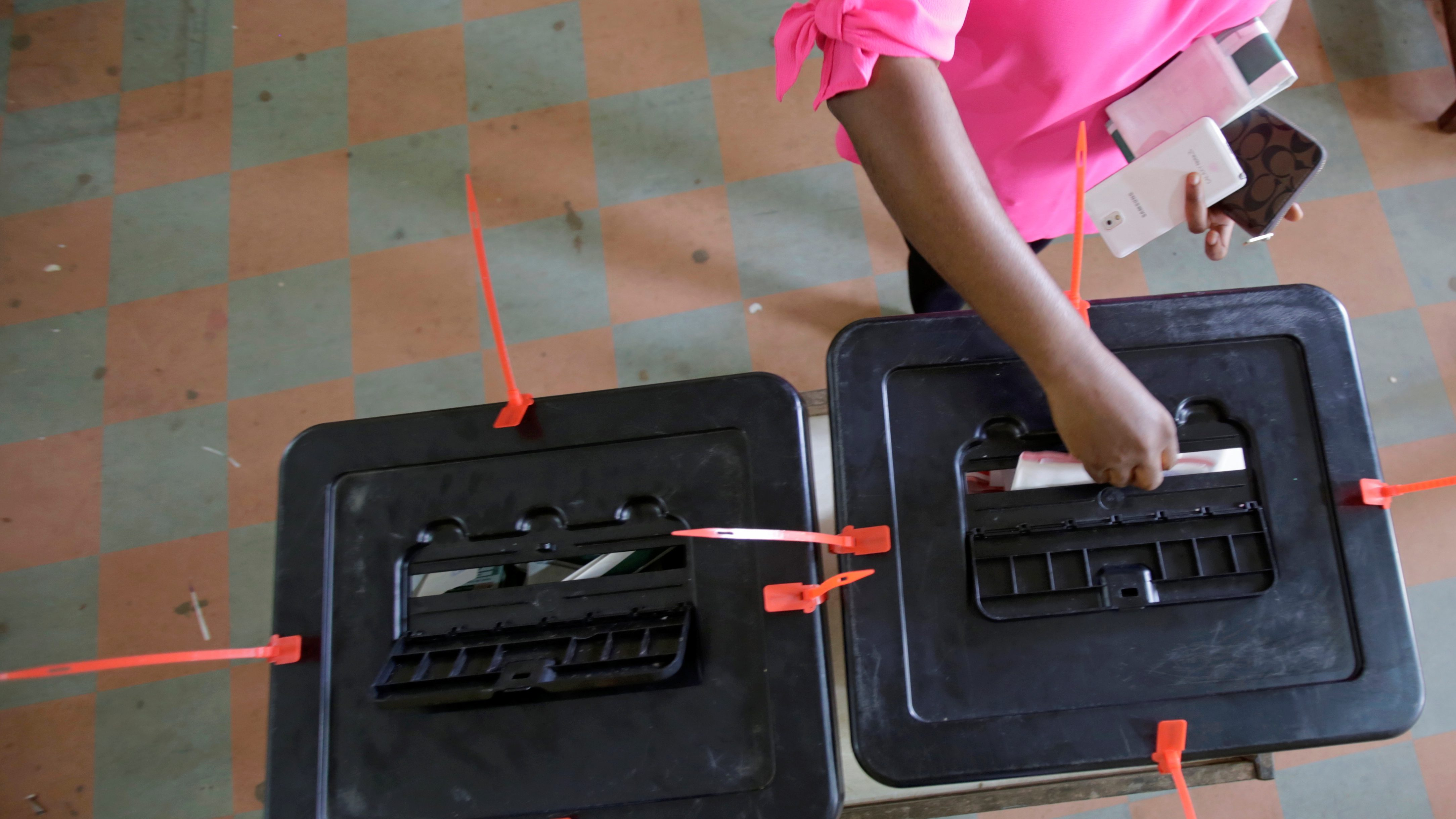 A woman casts her ballot during presidential elections at a polling station in Monrovia, Liberia, October 10, 2017.