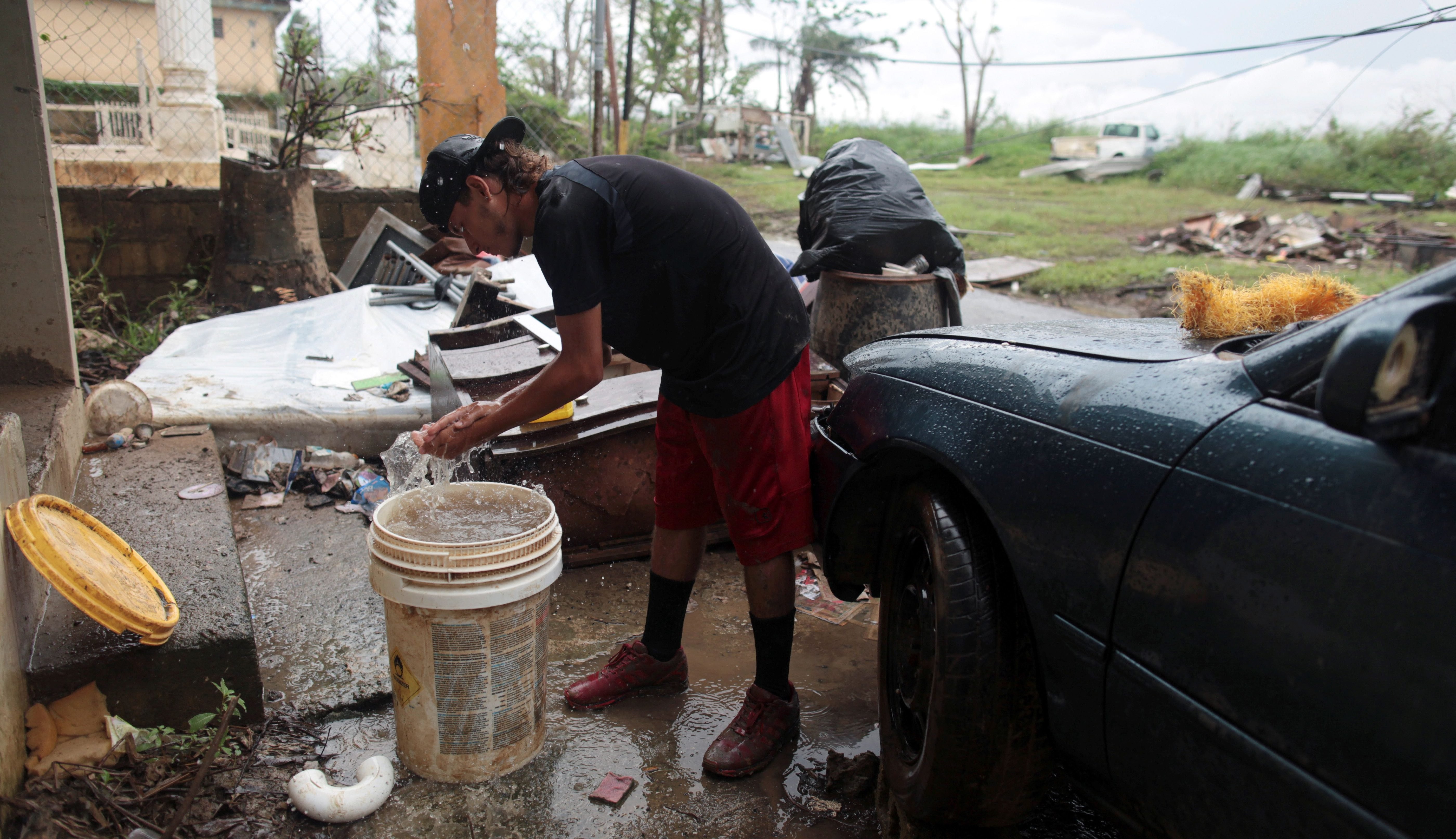 A man washes his hands with rainwater collected in a bucket, after the island was hit by Hurricane Maria, in Toa Baja, Puerto Rico October 16, 2017. REUTERS/Alvin Baez - RC1850864380