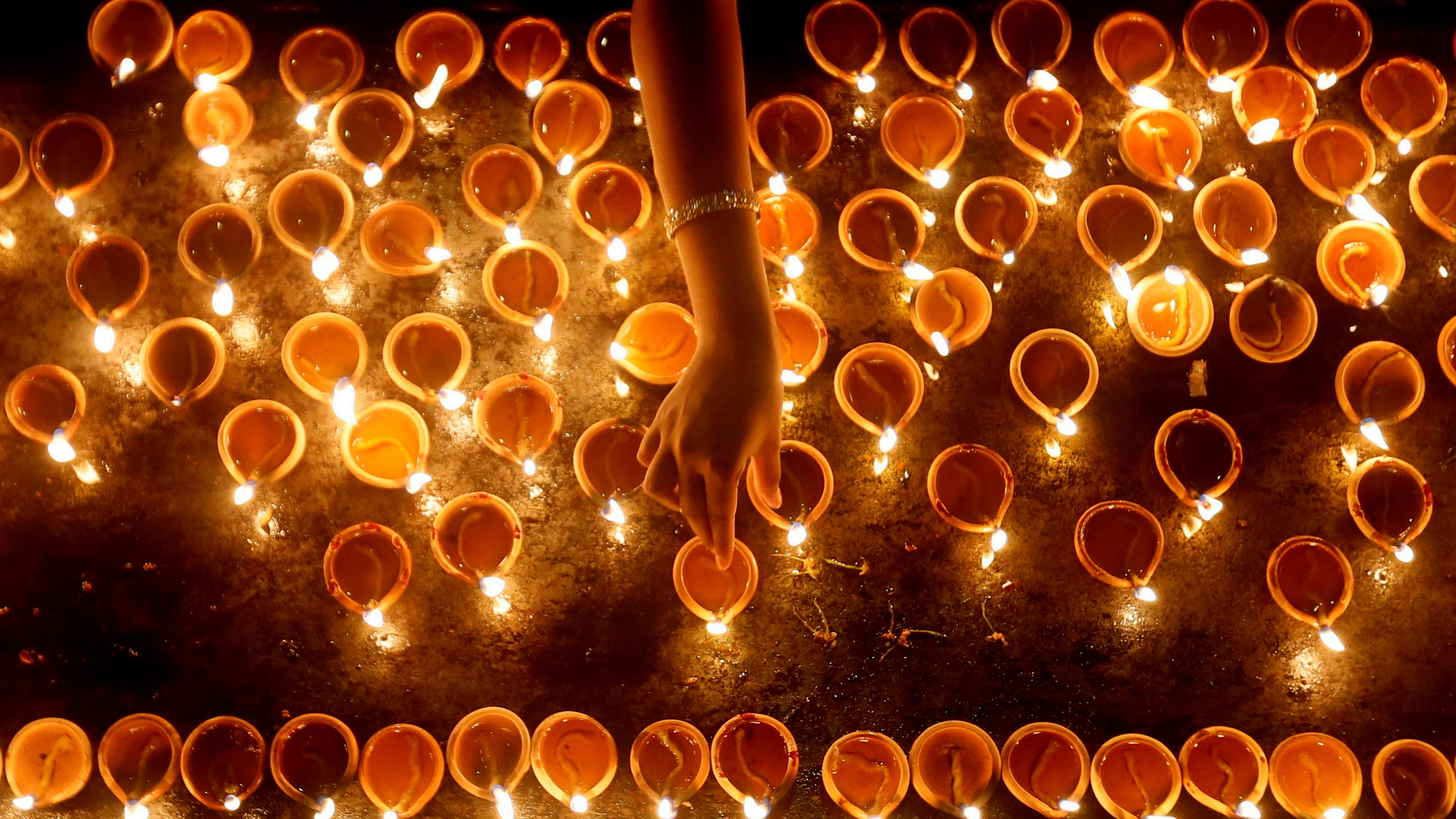 A devotee lights oil lamps at a religious ceremony during Diwali.