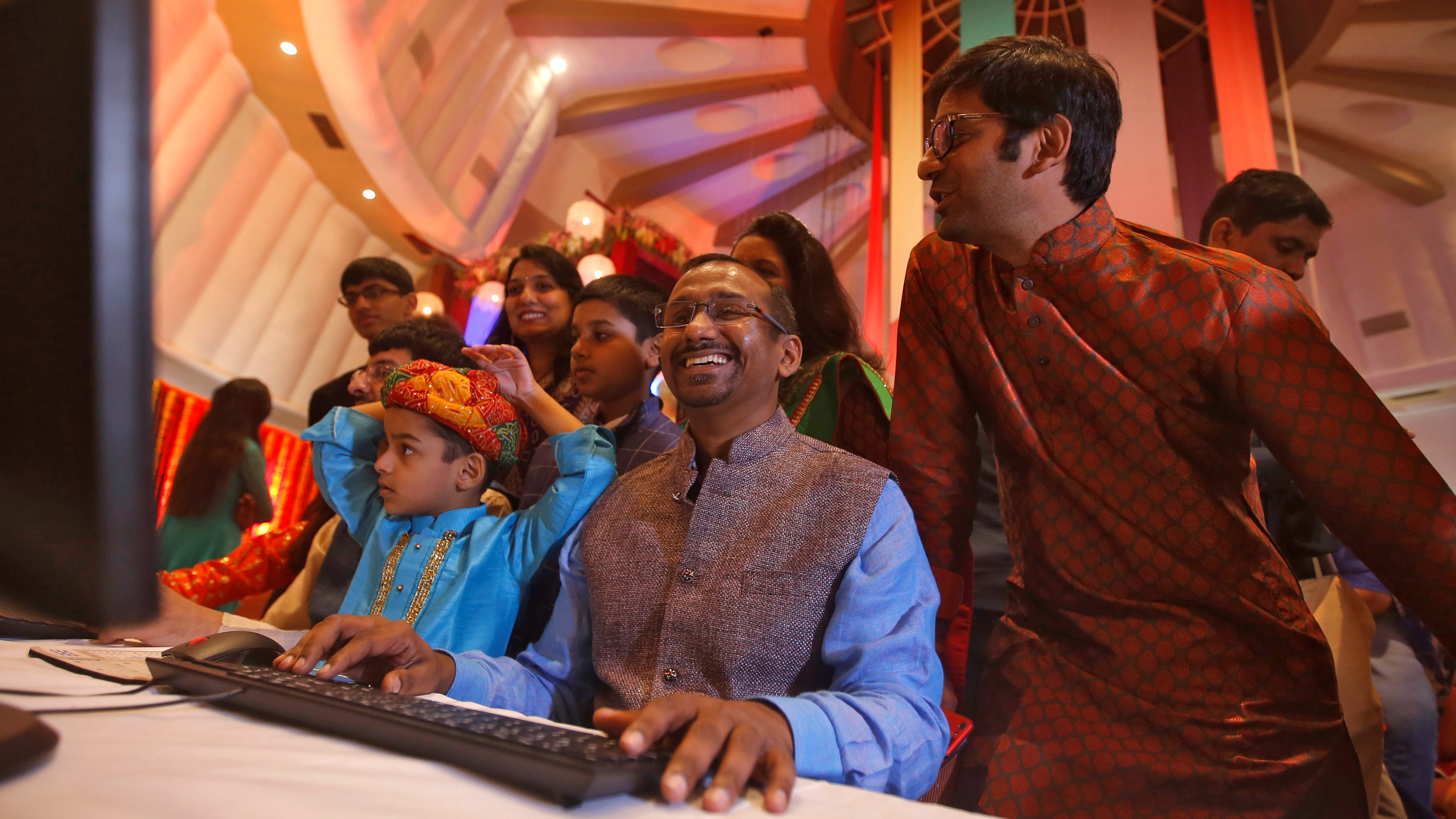 """A stockbroker trader reacts as his family watches him trading during a special """"muhurat"""" trading session for Diwali, the Hindu festival of lights, at BSE in Mumbai"""