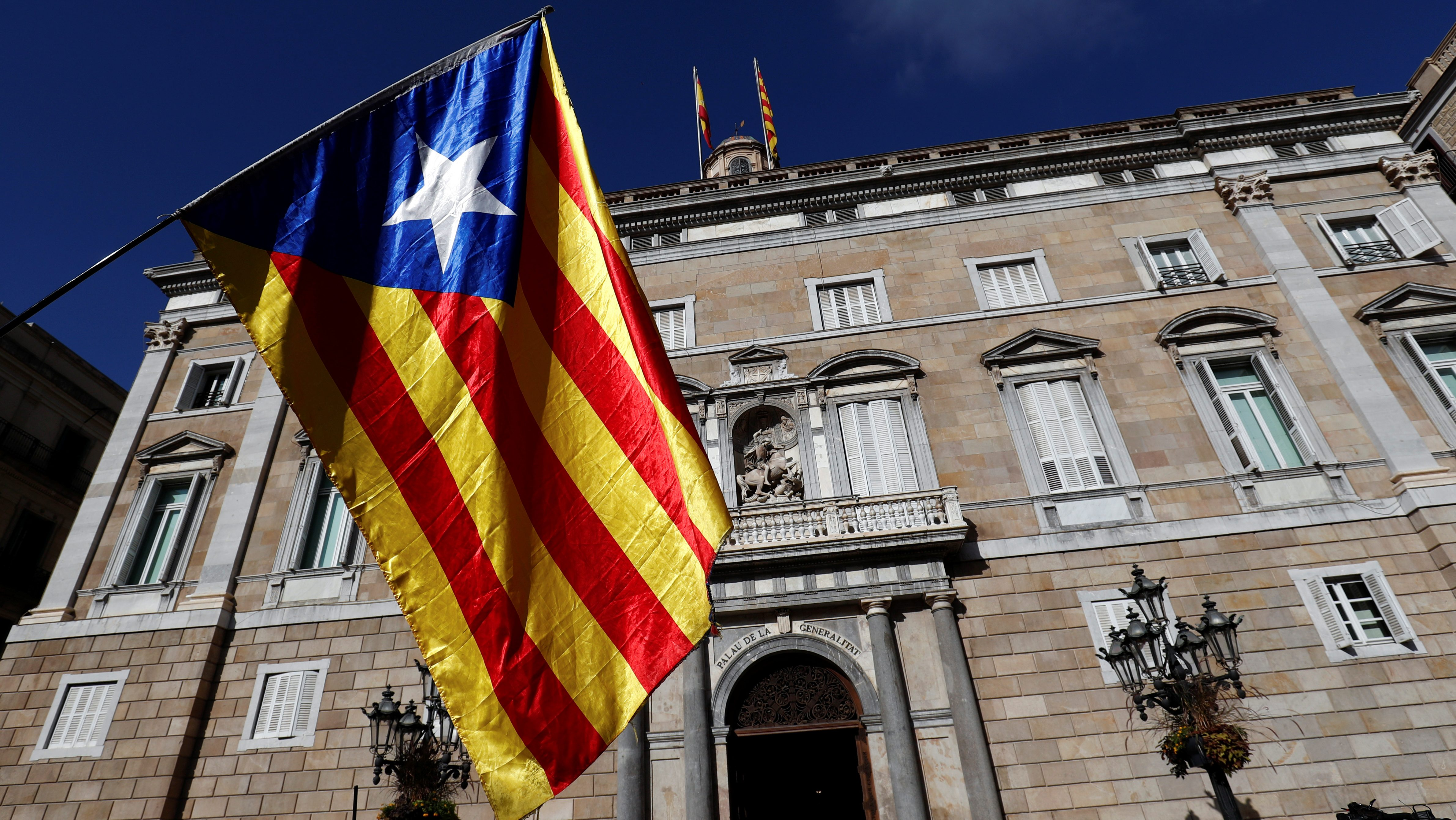 A Catalan separatist flag is waved in front of the Generalitat Palace, the Catalan regional government headquarters in Barcelona