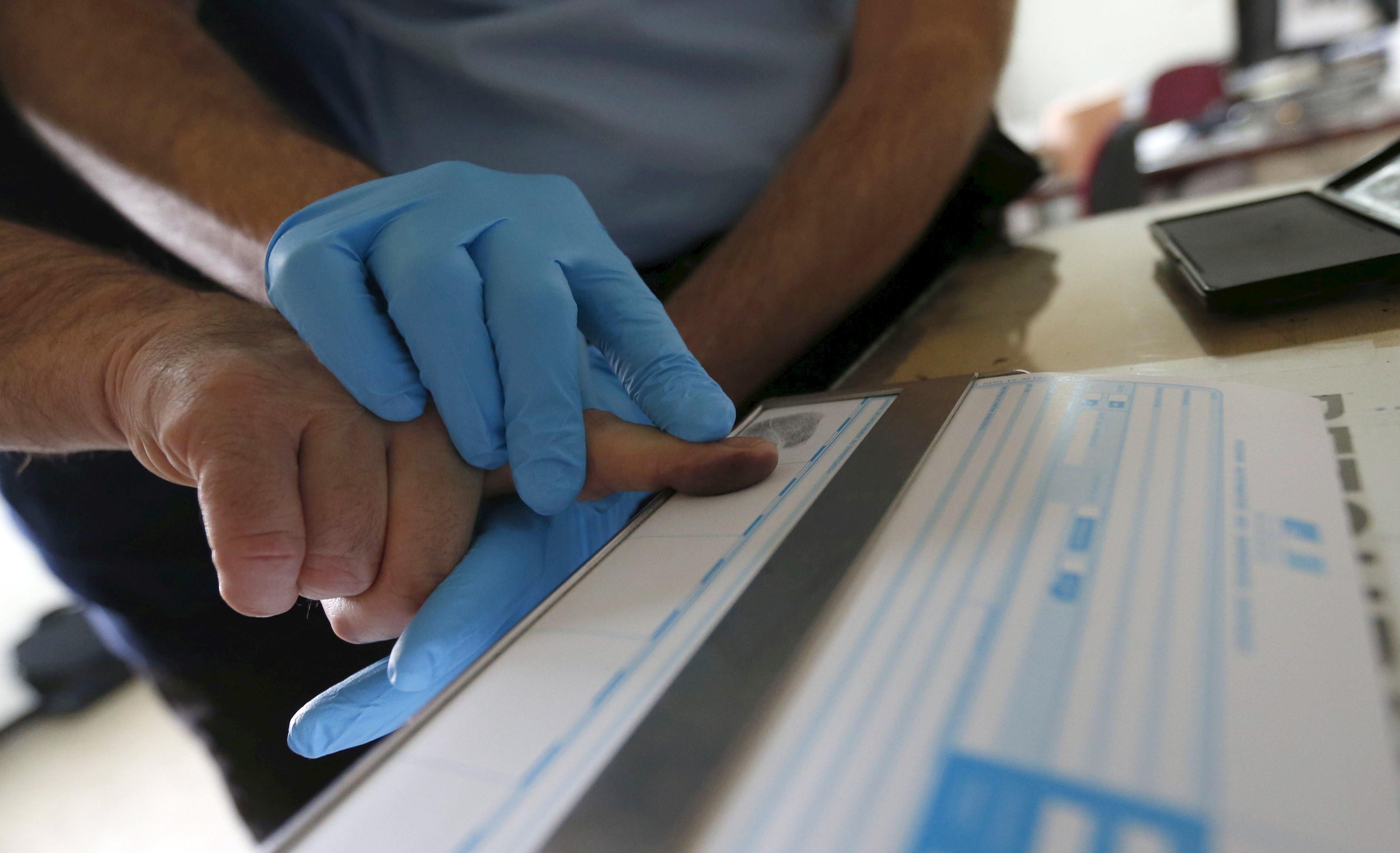 A French Gendarme takes a man's fingerprints in Bordeaux, Southwestern France, March 7, 2016.