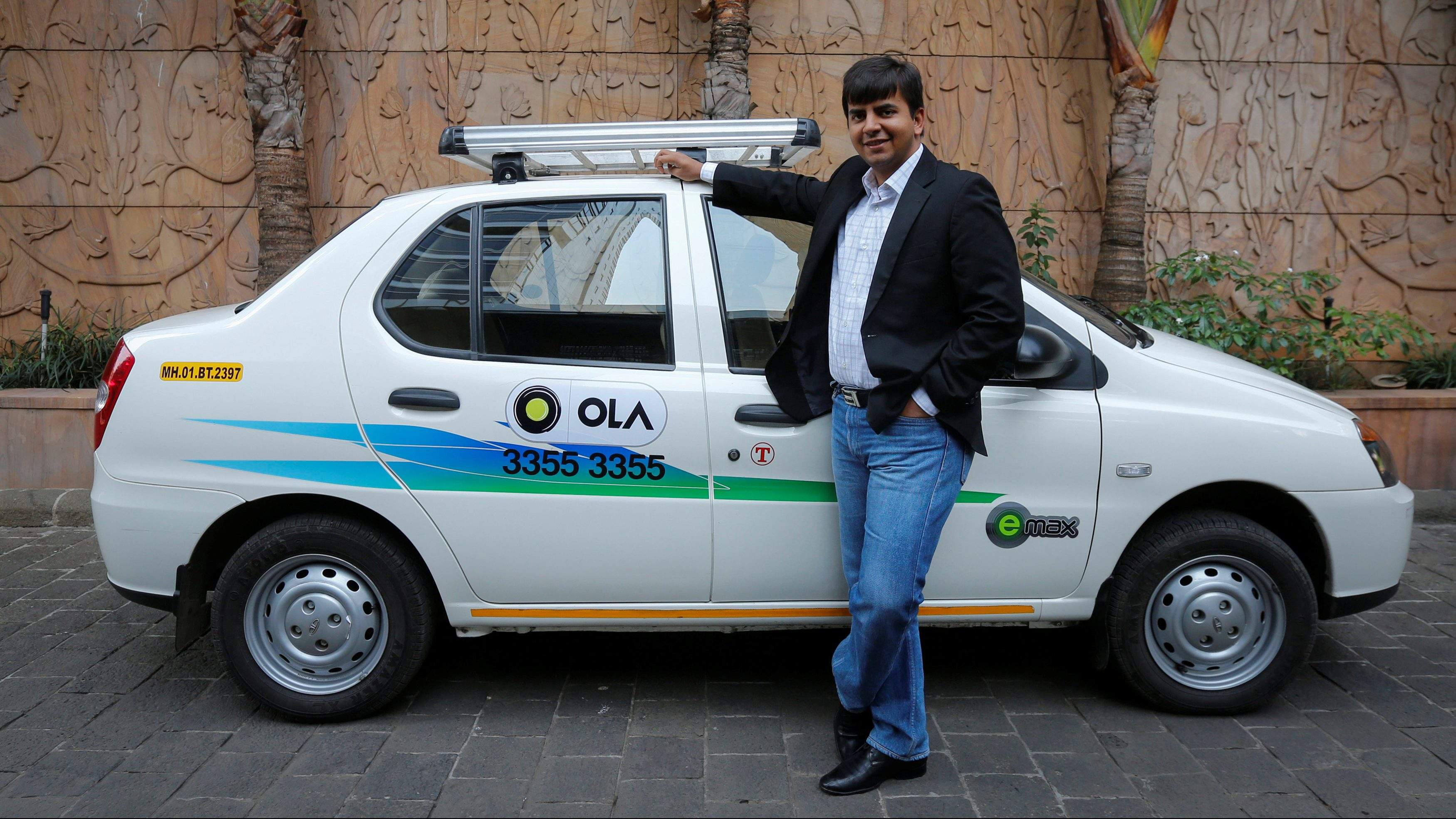 Bhavish Aggarwal, CEO and co-founder of Ola, an app-based cab service provider, poses in front of an Ola cab in Mumbai