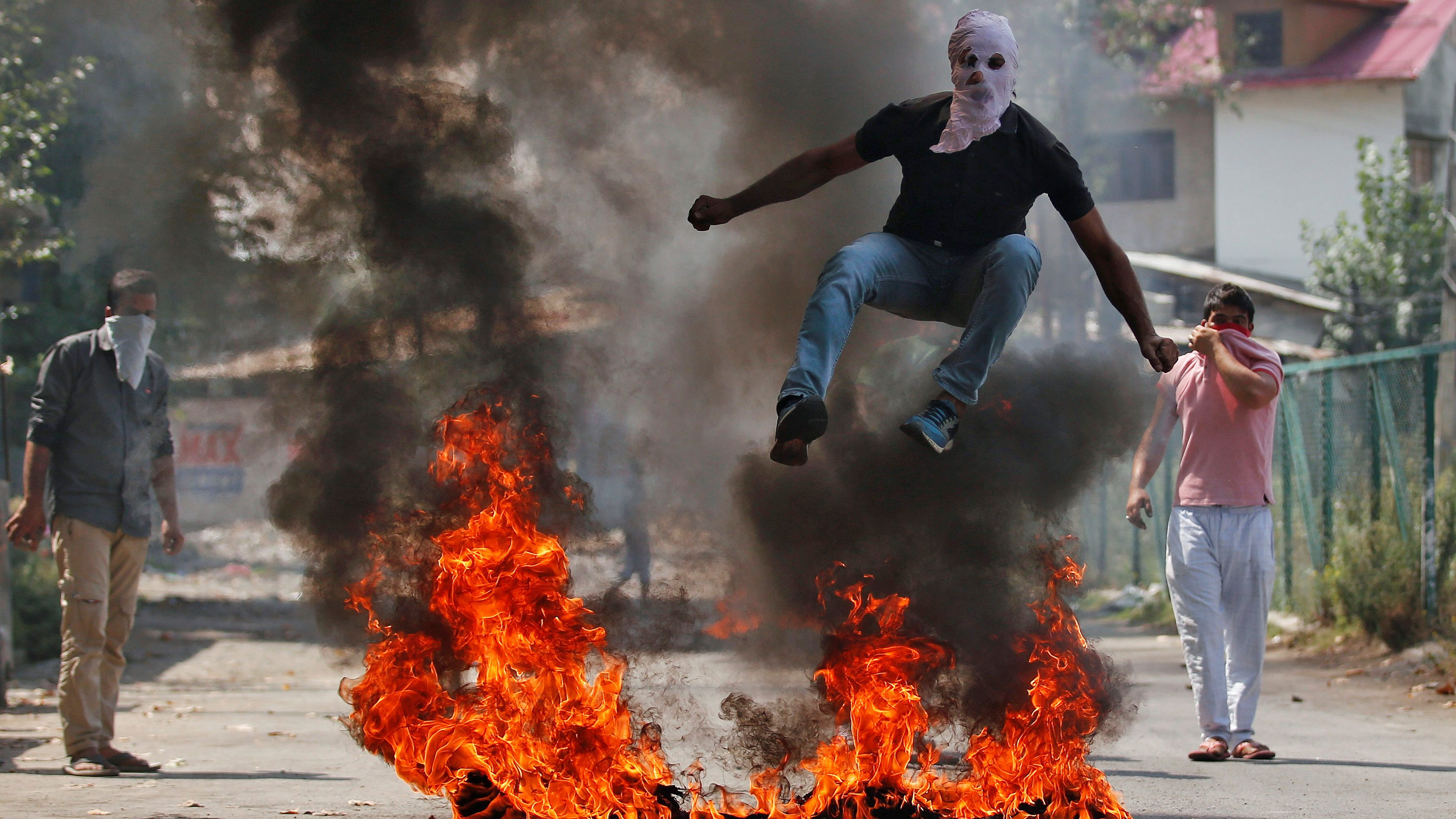 A man in a balaclava jumps over burning debris during a protest against the recent killings in Kashmir, in Srinagar