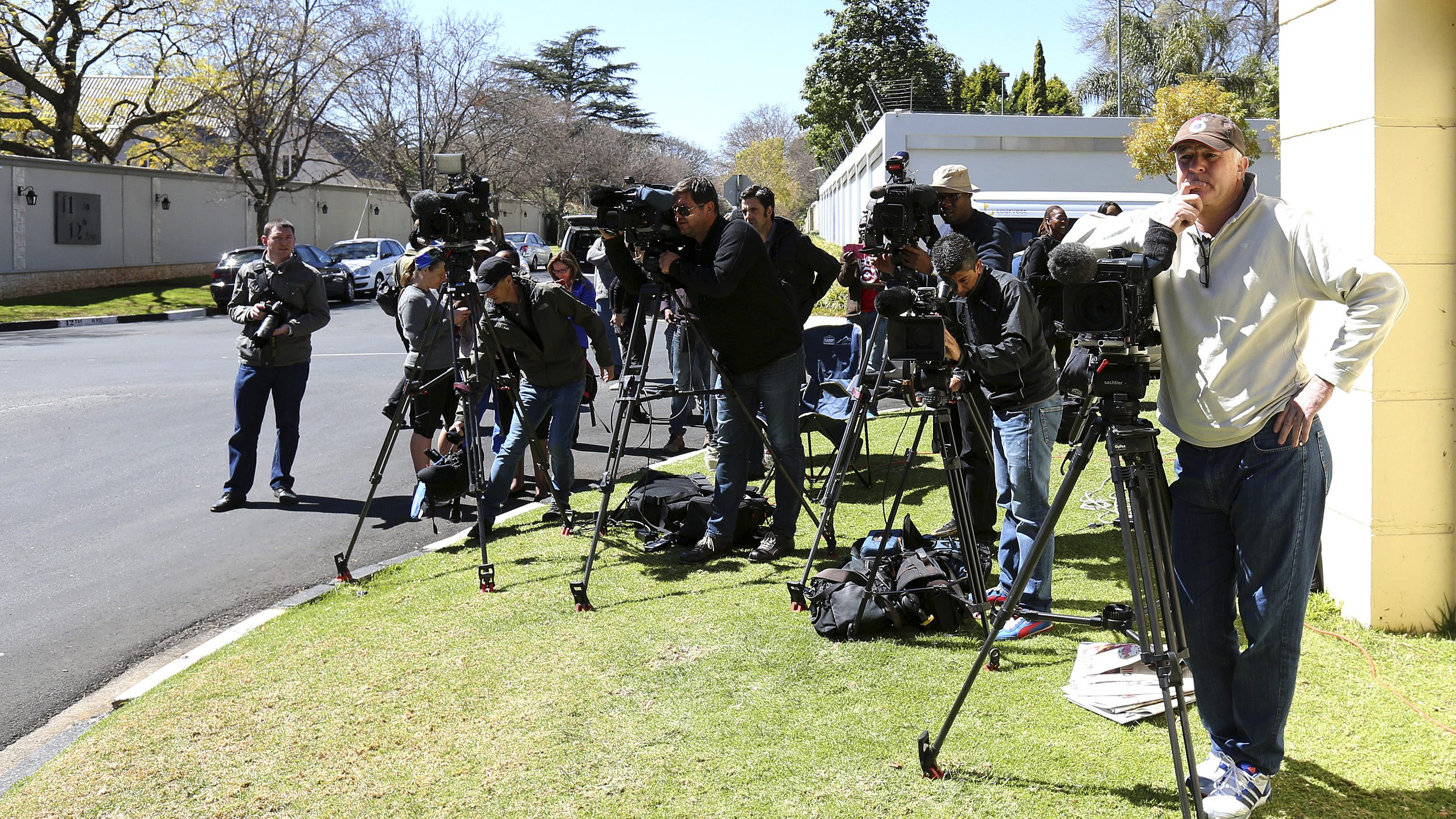 Members of the media stand outside former South African President Mandela's house in Houghton, Johannesburg