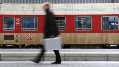 A businessman walks in front of a Deutsche Bahn train in Berlin