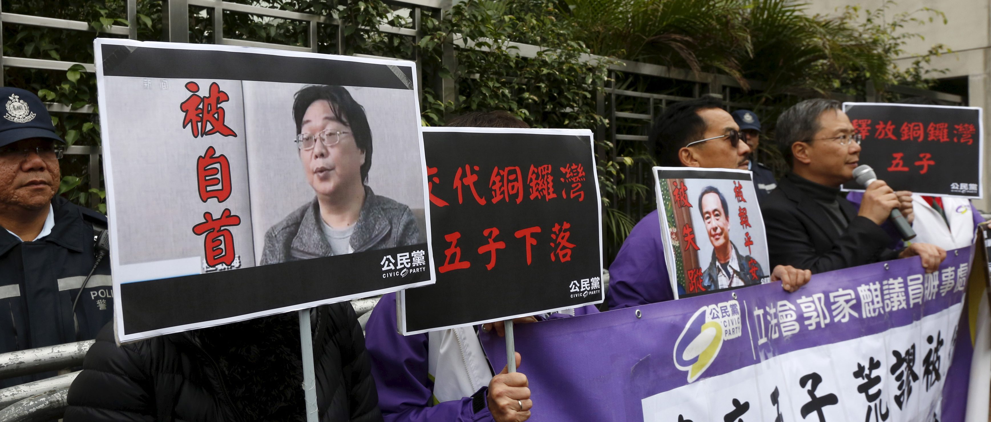 Members from the pro-democracy Civic Party carry a portrait of Gui Minhai and Lee Bo during a protest outside the Chinese Liaison Office in Hong Kong