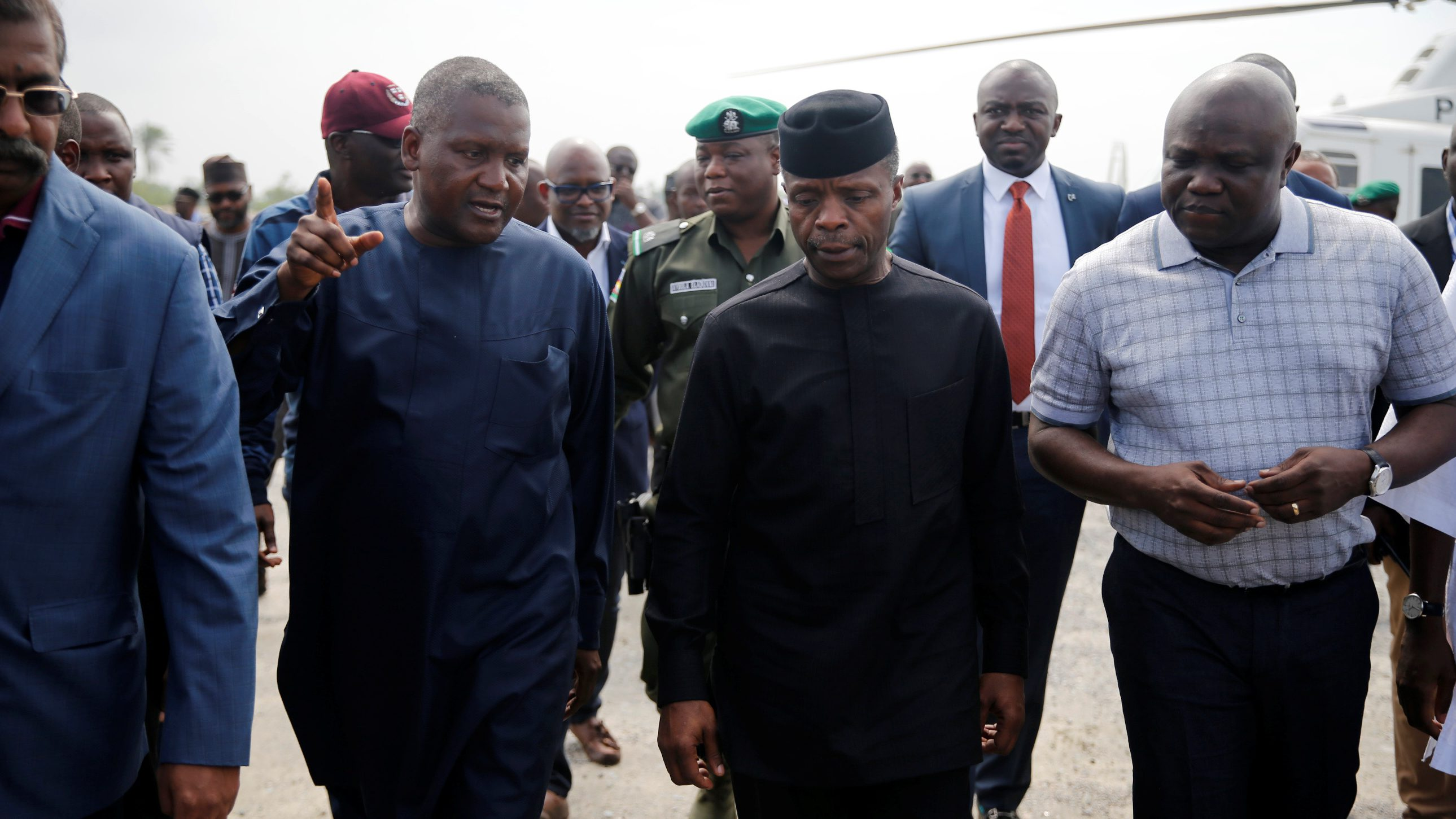 Africa's richest man, Aliko Dangote, Nigeria's Vice-President Yemi Osinbajo and Lagos' Governor Akinwunmi Ambode walk as they arrive for a facility tour at the proposed Dangote oil refinery site near Akodo beach in Lagos