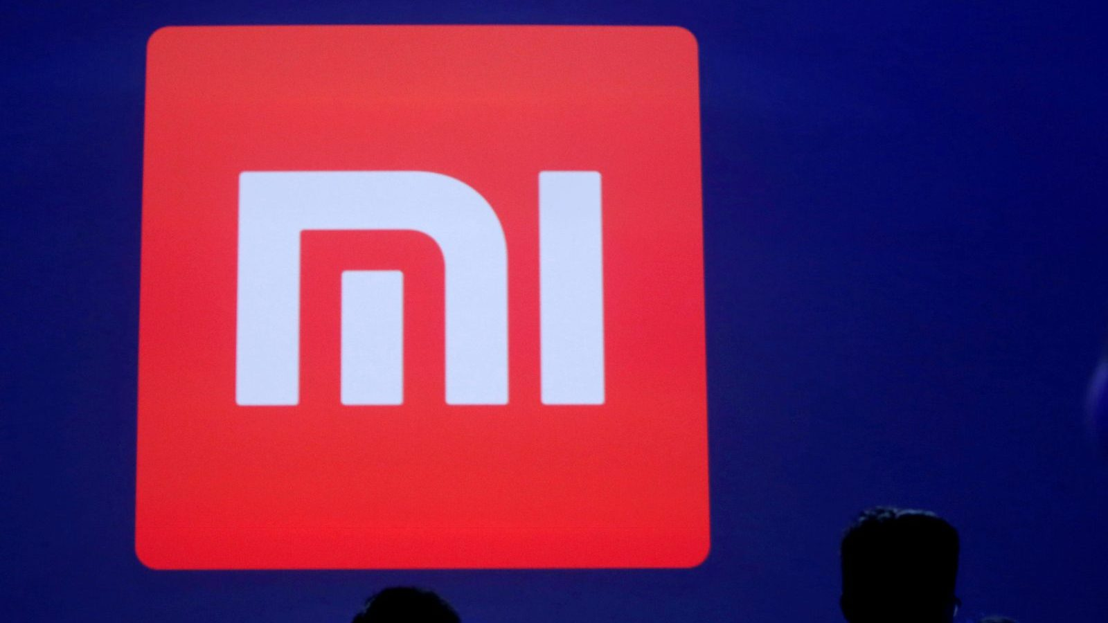 Attendants are silhouetted in front of Xiaomi's logo at a venue for the launch ceremony of Xiaomi's new smart phone Mi Max in Beijing, May 10, 2016. REUTERS/Kim Kyung-Hoon/File Photo - S1AEUACJUDAA