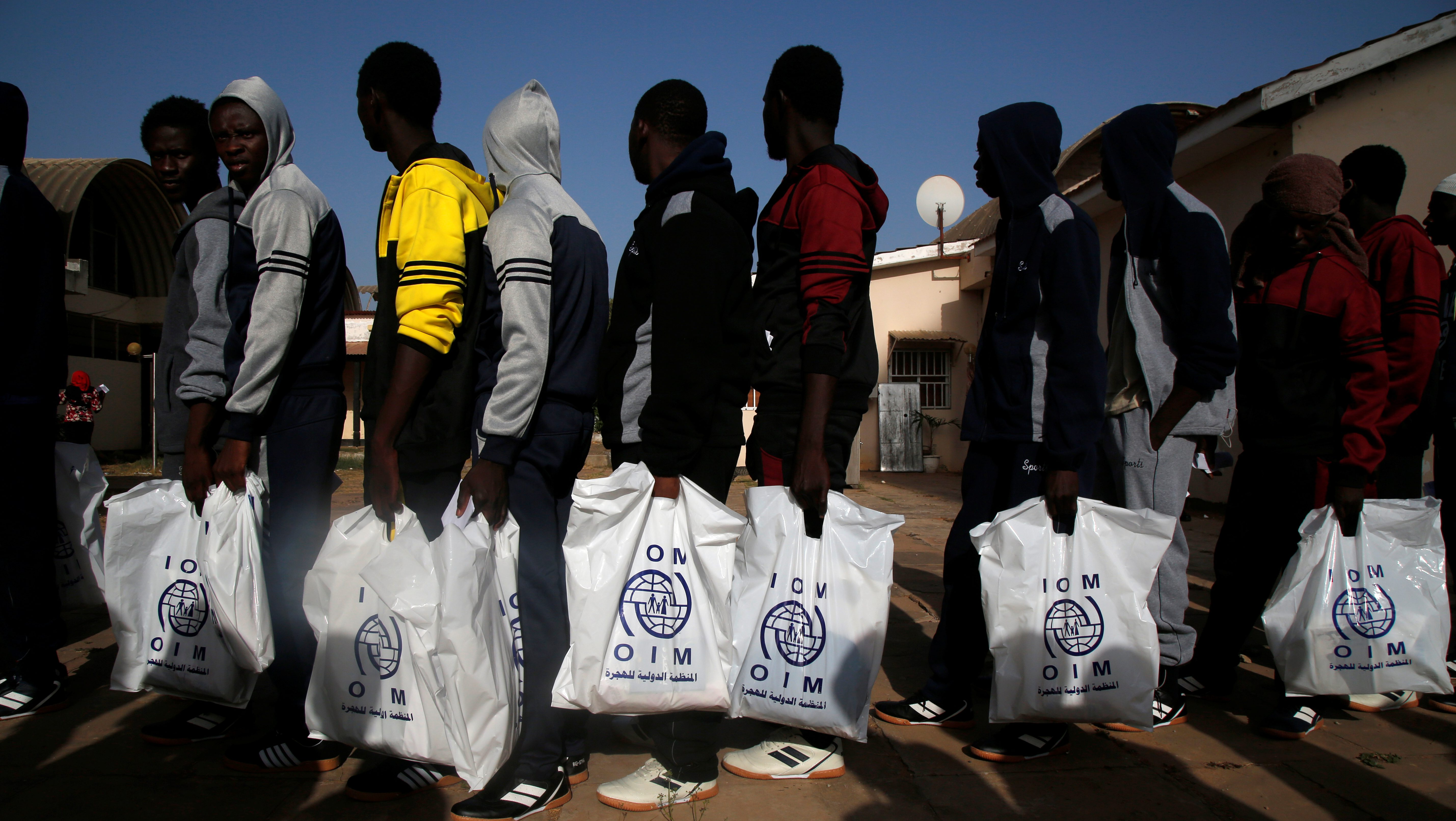 Gambian migrants who voluntarily returned from Libya stand in line as they wait for registration at the airport in Banjul