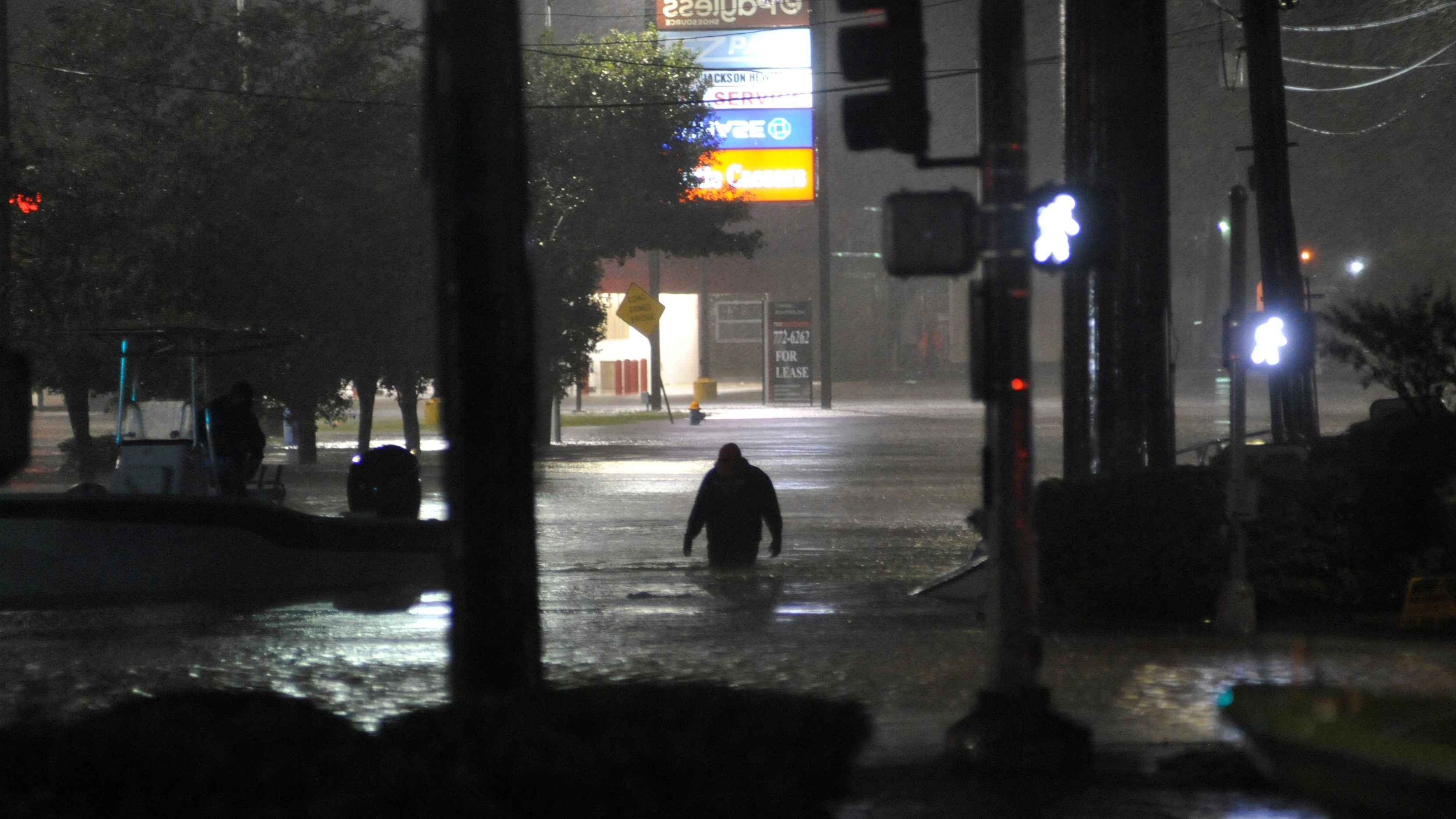A man wades through floodwater after Hurricane Harvey inundated the Texas Gulf coast with rain causing widespread flooding, in Houston