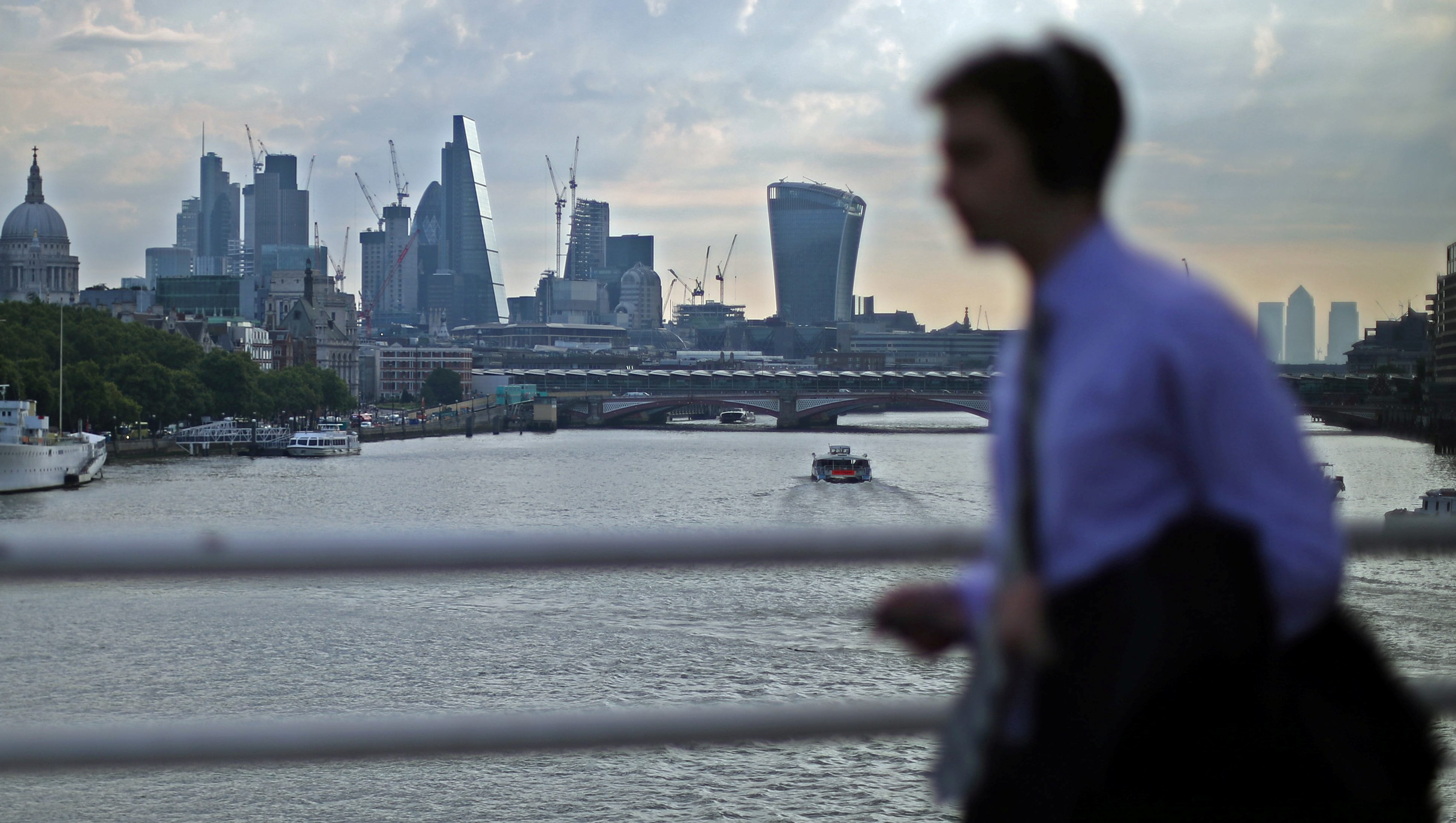 A commuter walks across Waterloo bridge during the morning rush hour in London,