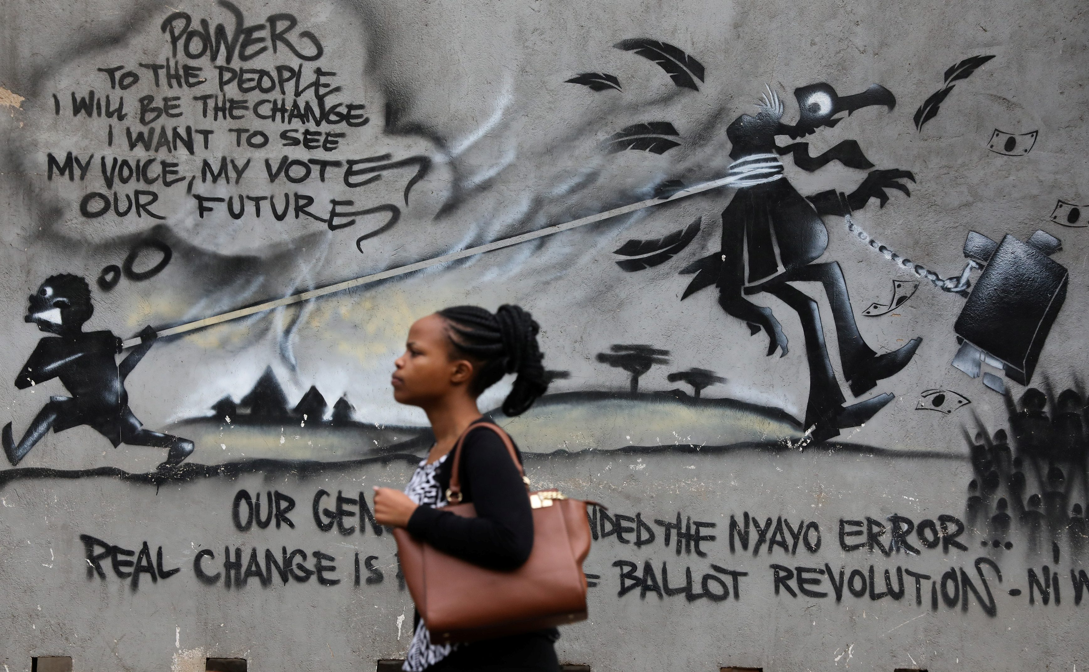 A woman walks past a wall graffiti in the central business district of Nairobi, Kenya October 23, 2017.